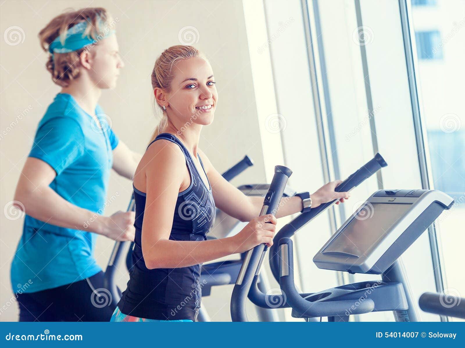 Jovens no gym moderno no simulador da corrida