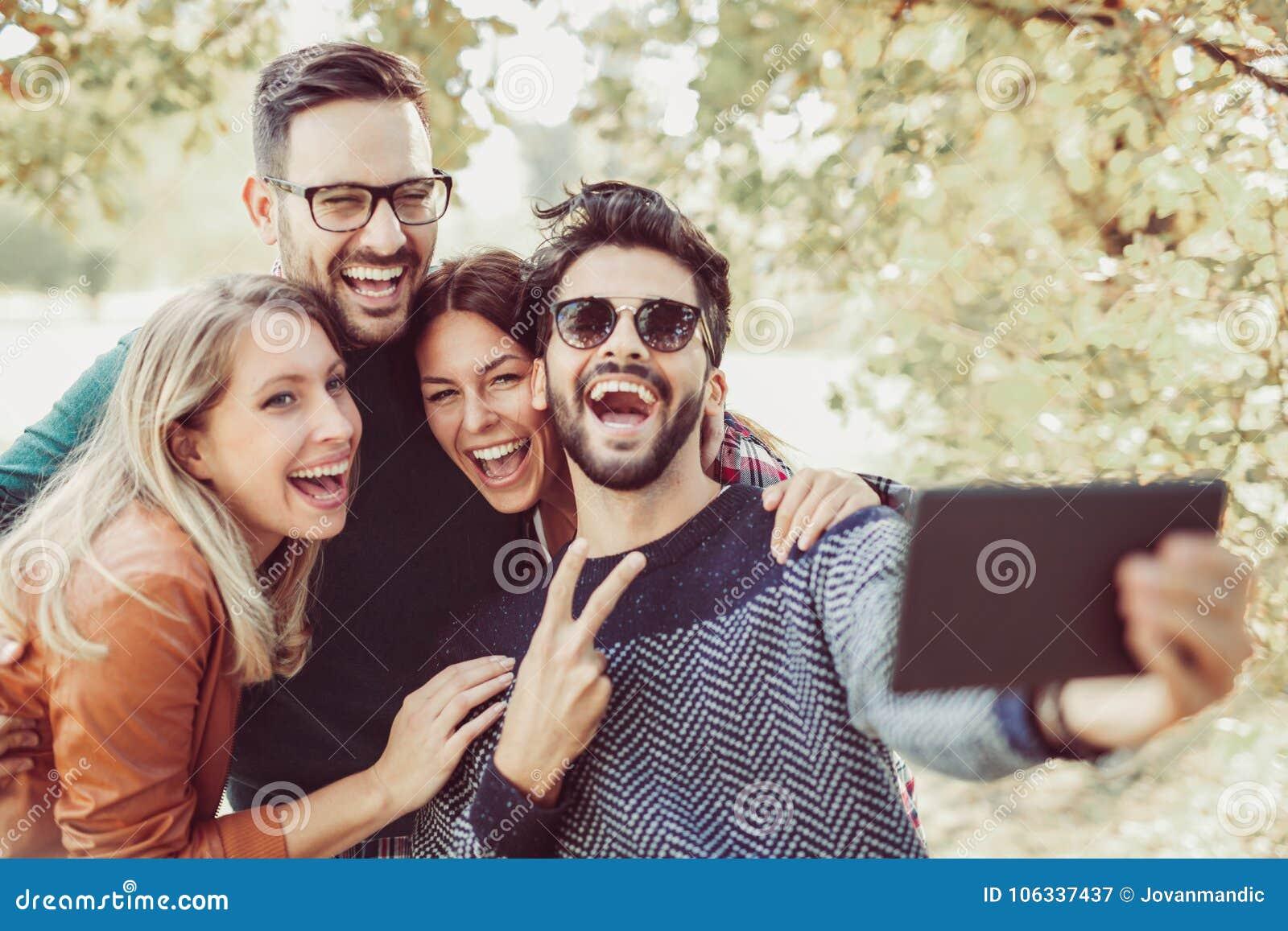 Jovens no parque com a tabuleta digital que tem o divertimento