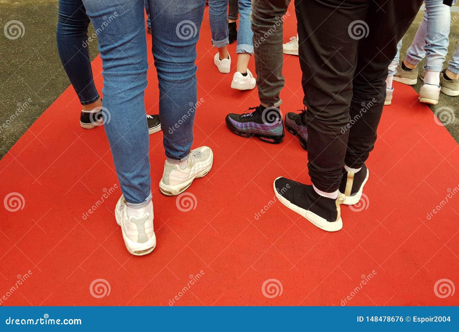 Jovens no tapete vermelho Pés em sapatas dos esportes