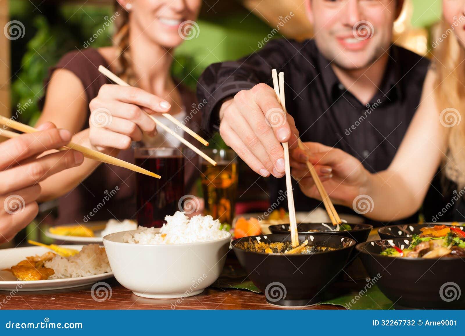 Jovens que comem no restaurante tailandês