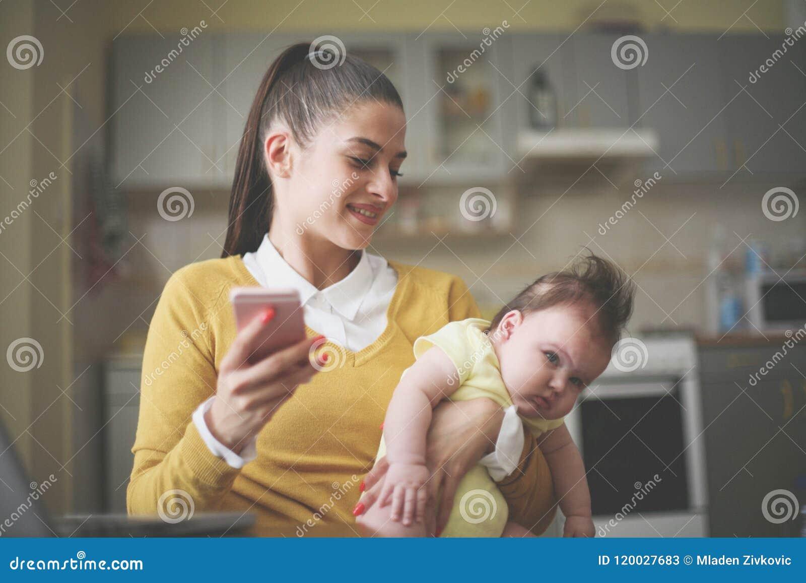 Jovens que guardam seu bebê nos braços e que usam o móbil