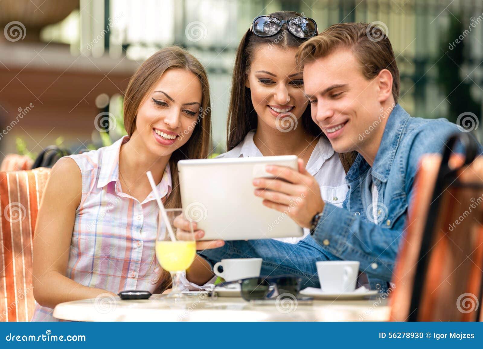 Jovens que olham o PC da tabuleta no café fora