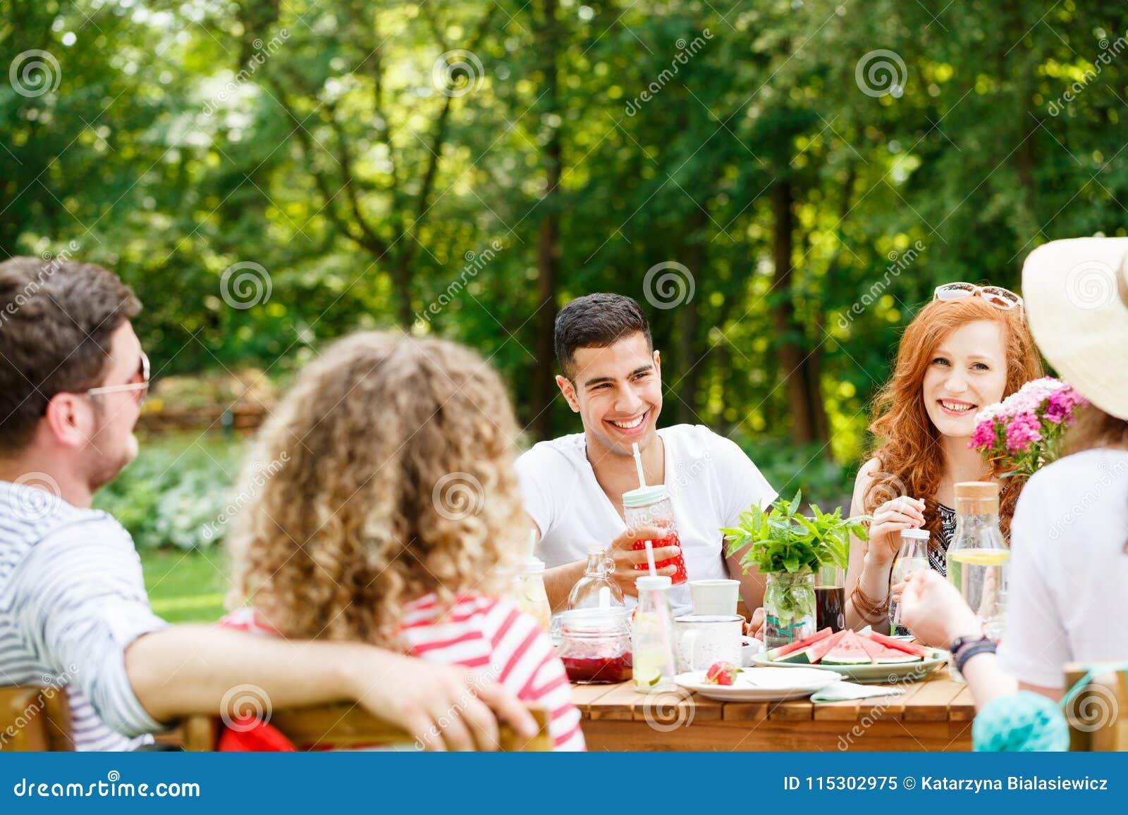 Jovens que riem e que comem