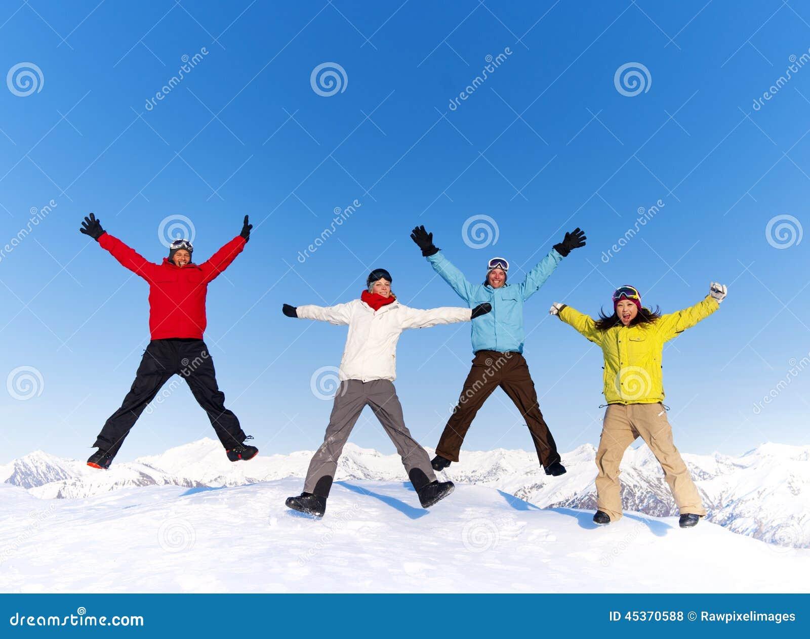 Jovens que saltam na neve e que apreciam o inverno