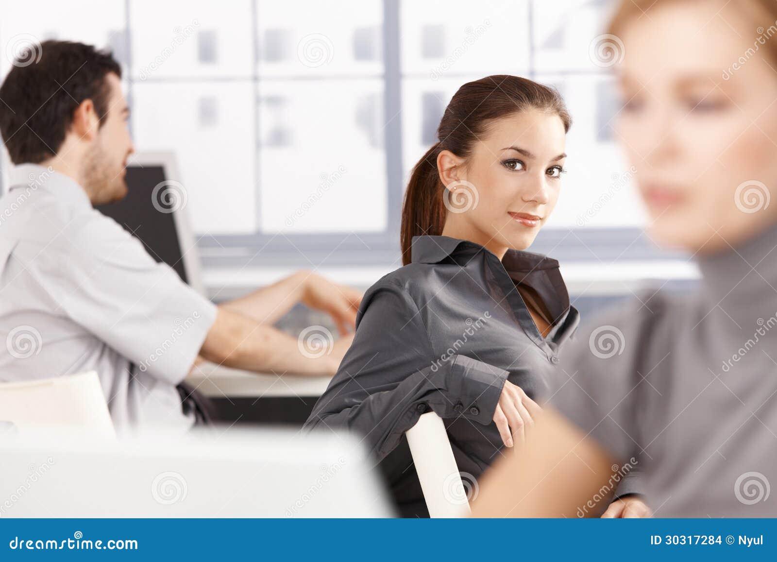 Jovens que trabalham no sorriso do escritório