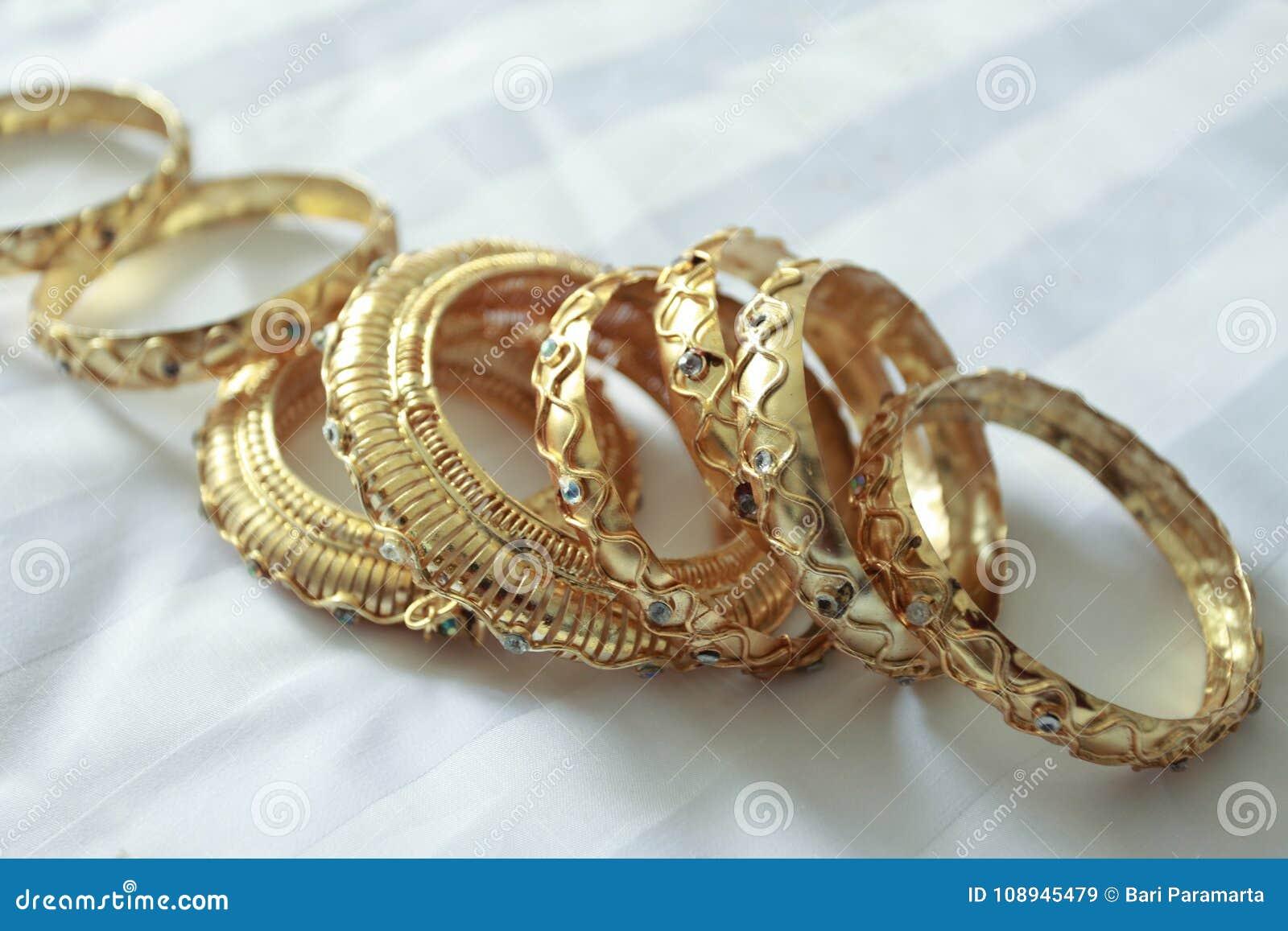 92859dd07bc2 Una pulsera de imitación del oro usada en la muñeca sirve hacer al portador  hermoso