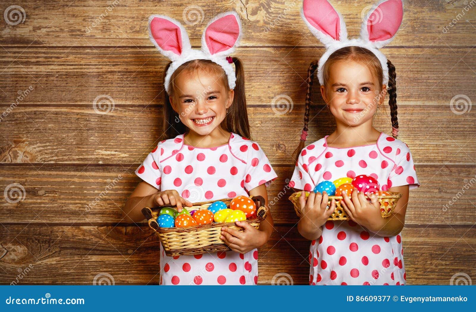 Joyeuses Pâques ! soeurs mignonnes de filles de jumeaux habillées comme lapins avec e