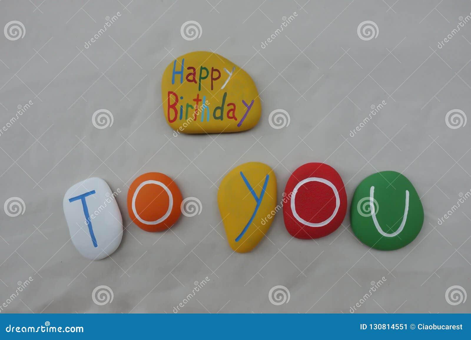 Joyeux anniversaire avec une composition colorée en pierres au-dessus du sable blanc