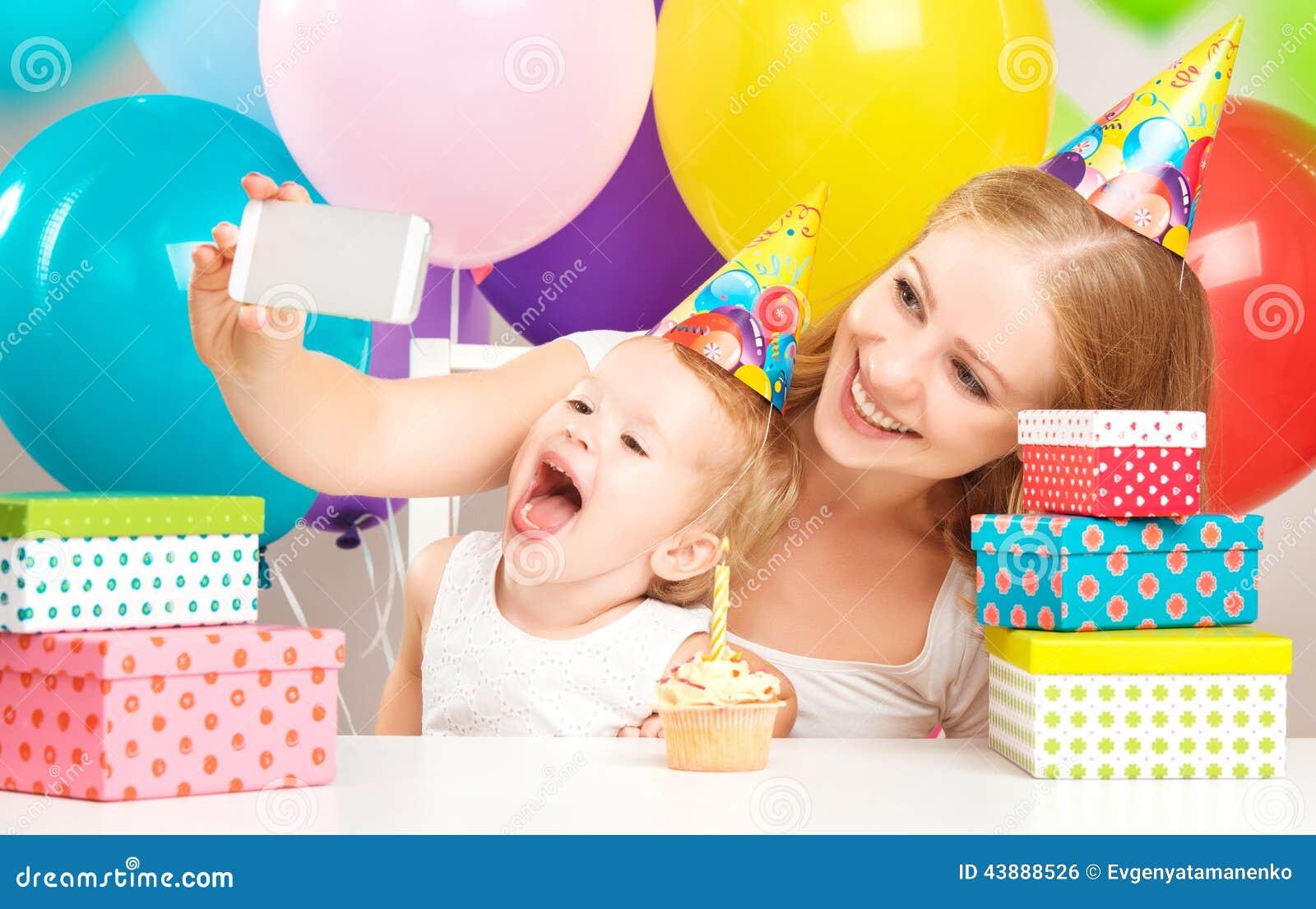 Joyeux anniversaire Selfie la mère a photographié sa fille l enfant d anniversaire avec des ballons, gâteau, cadeaux