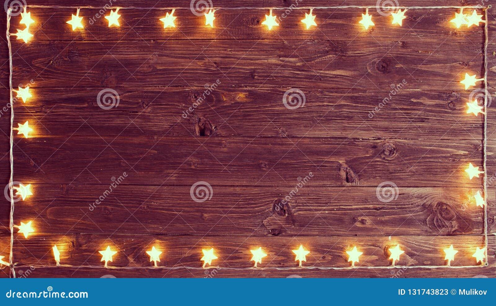 Joyeux Noël ! Cadre de lumières de Noël sur le fond en bois avec l espace de copie