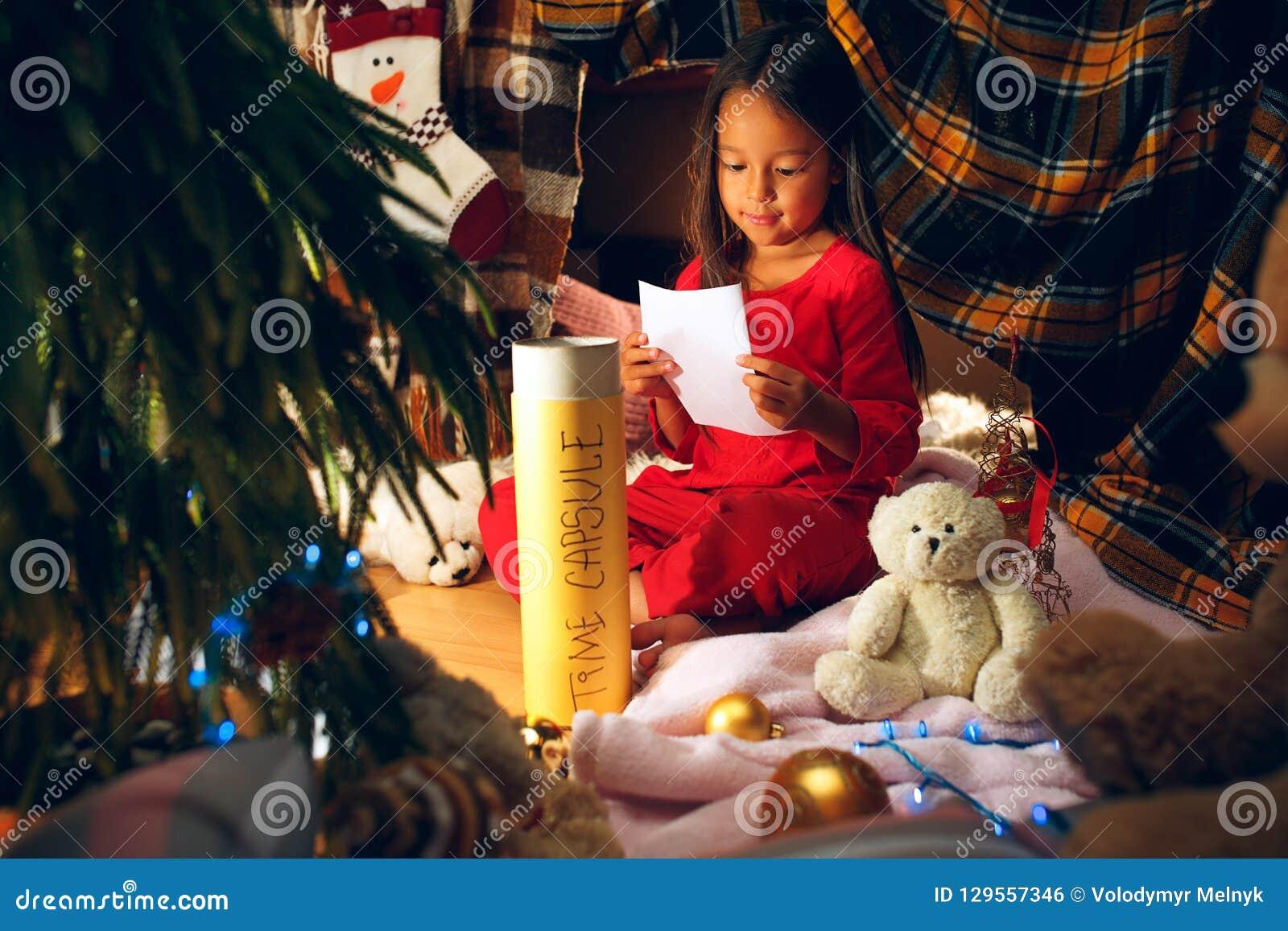 Joyeux Noël et bonnes fêtes La fille mignonne de petit enfant écrit la lettre à Santa Claus près de l arbre de Noël