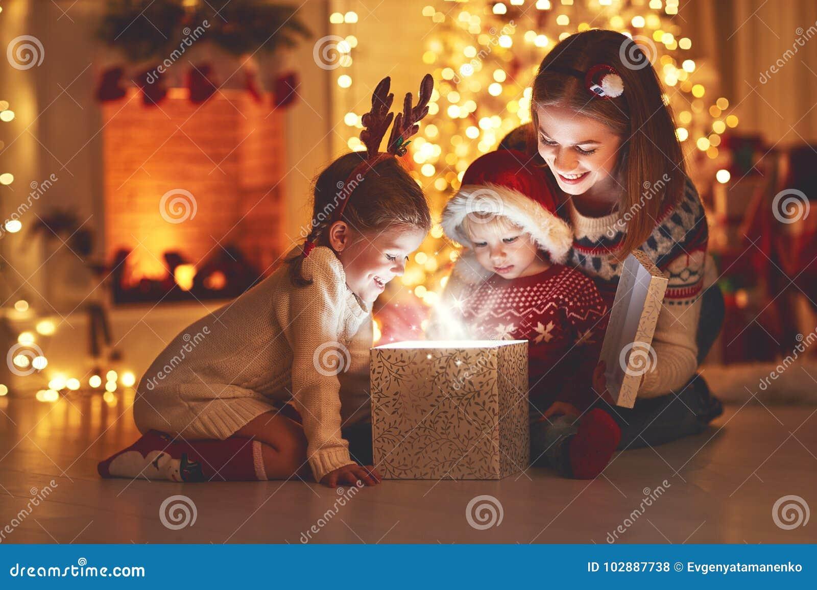 Joyeux Noël ! mère et enfants de famille avec le cadeau magique à