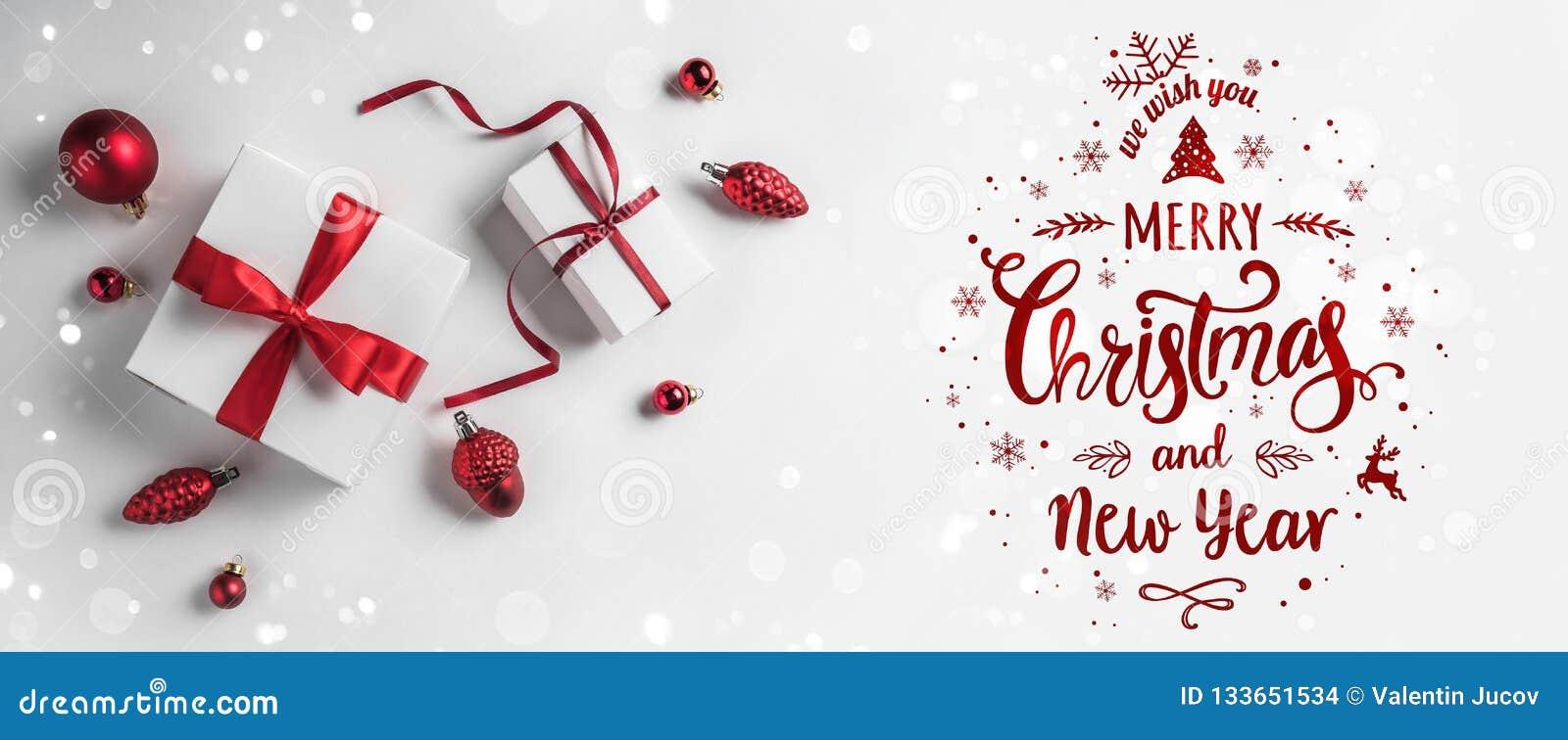 Joyeux Noël typographique sur le fond blanc avec les boîte-cadeau et la décoration rouge