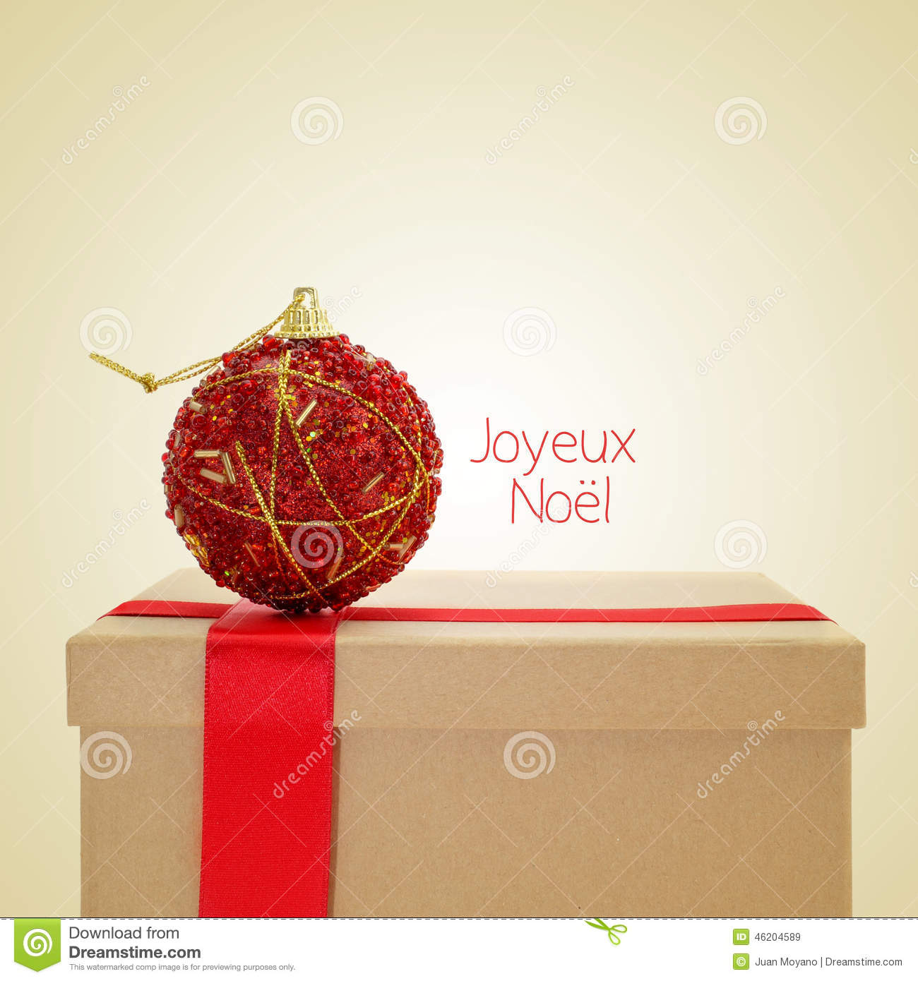 Gift with a red ribbon and a christmas ball and the sentence joyeux