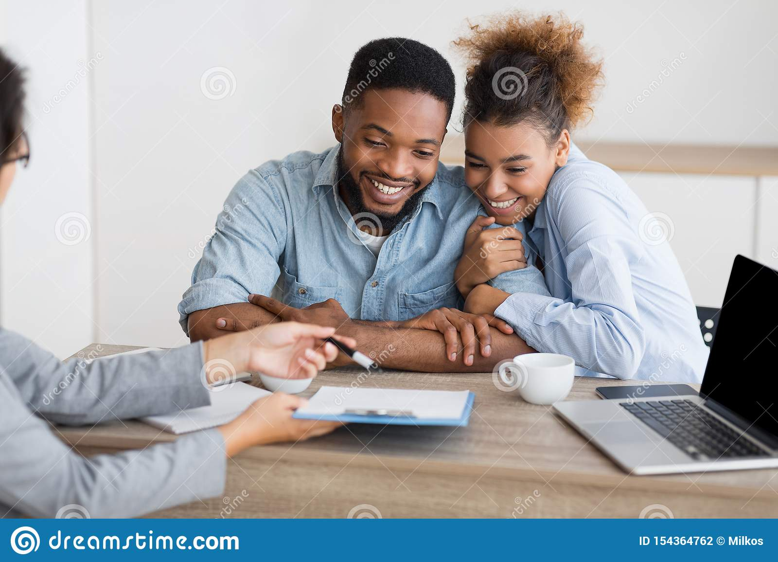 Joyful afro couple sitting at family counselor`s office