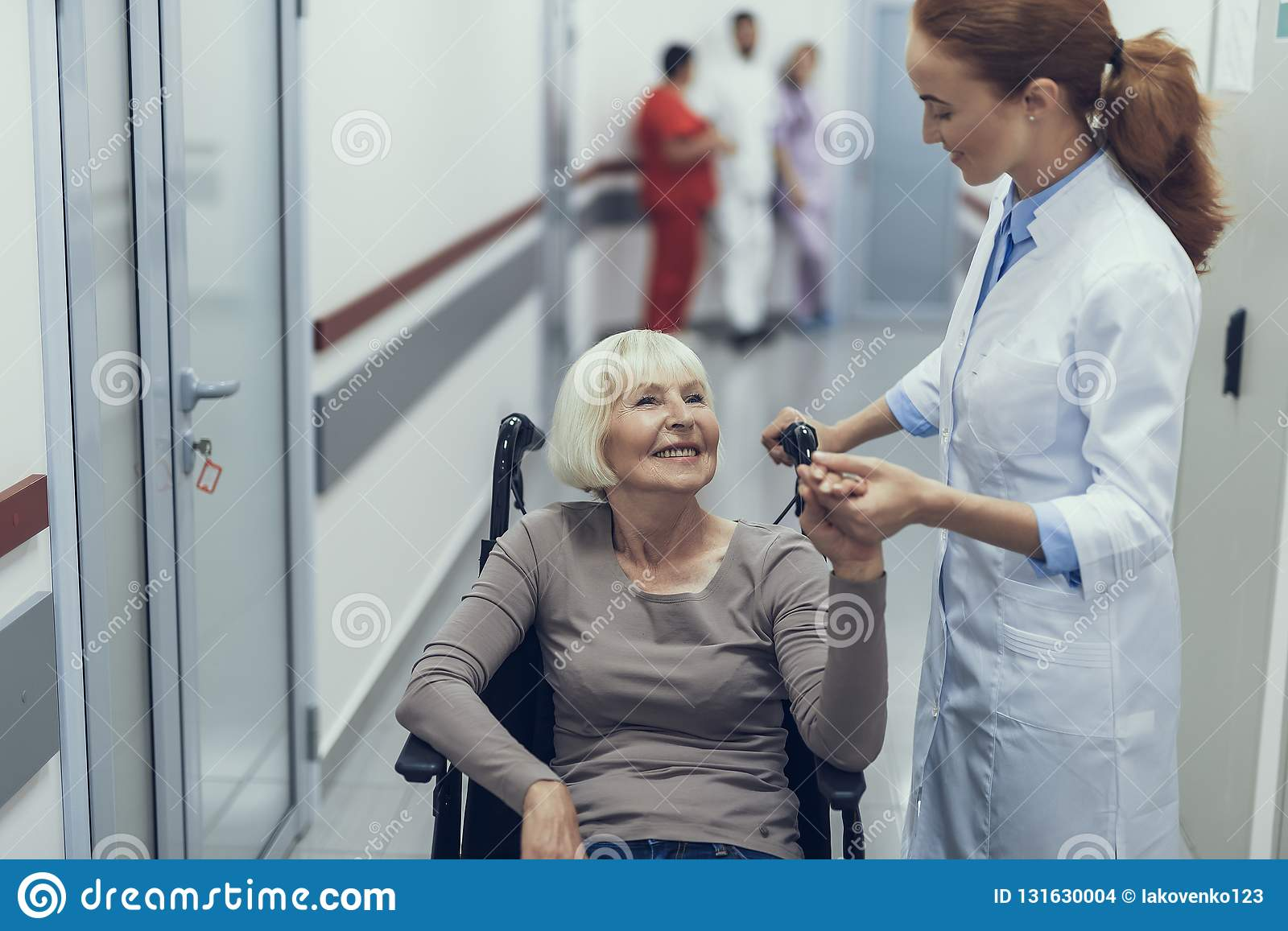 Cheerful lady on pushchair is talking to female doctor