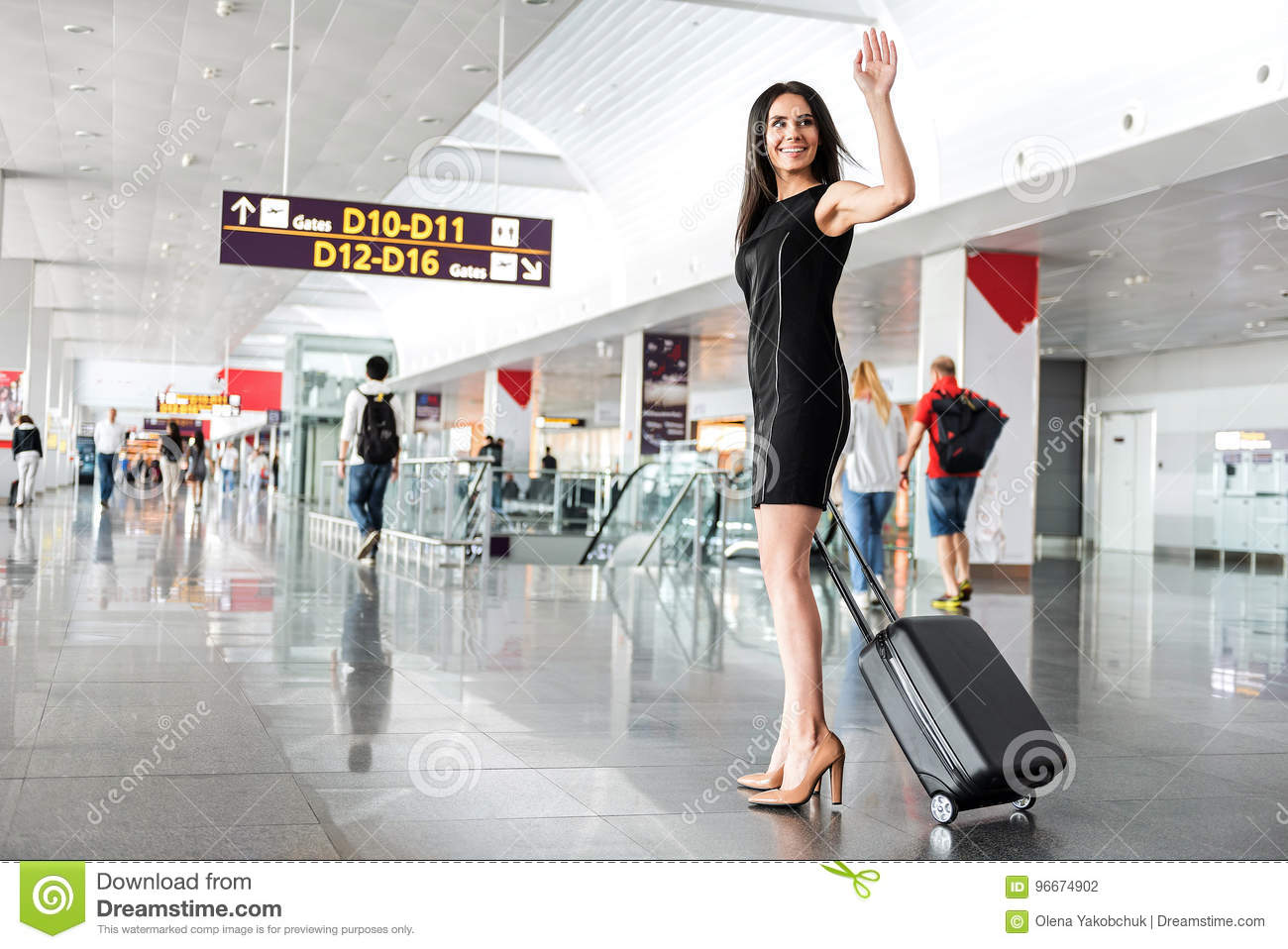 Joyful attractive lady is standing with luggage
