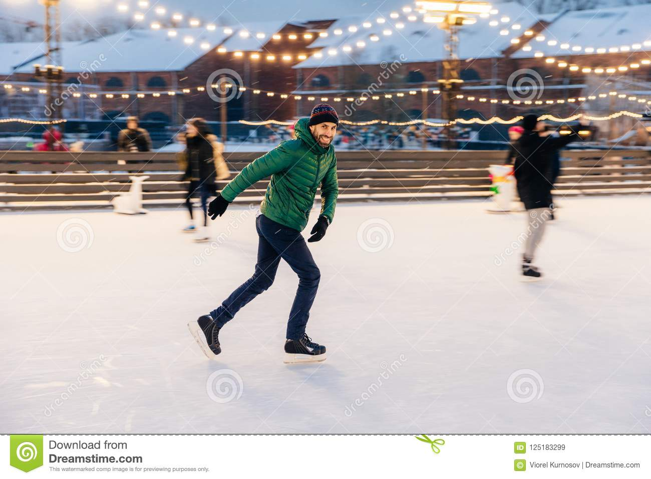 Joyful bearded man practices going skating on ice ring, has cheerful expression, smiles happily, demontrates his professionalism.