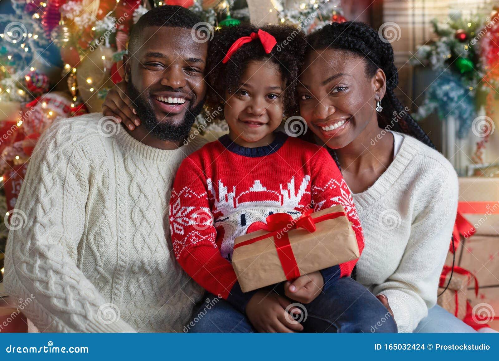Joyful Black Family Of Three Posing With Gift Near ...