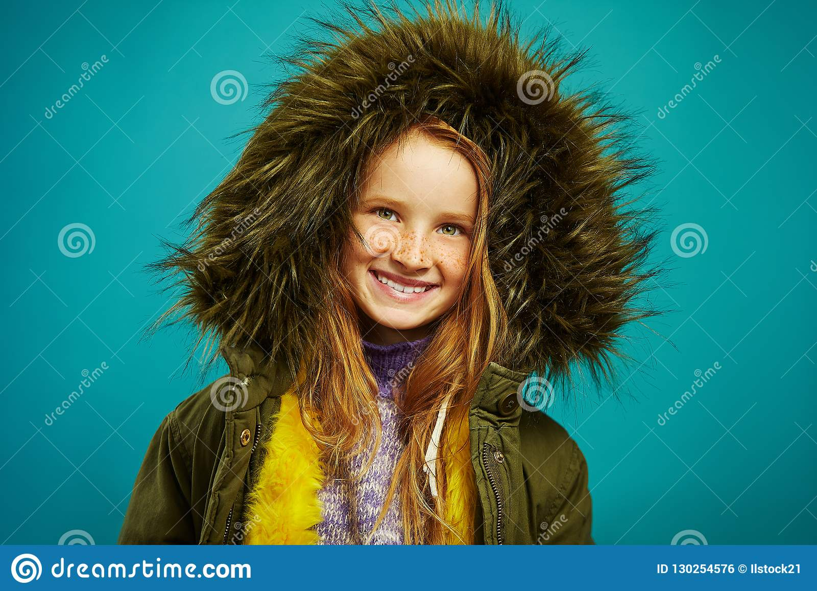 Joyful children girl in demi season winter jacket isolated on blue background. Smiling teenage child expresses sincere