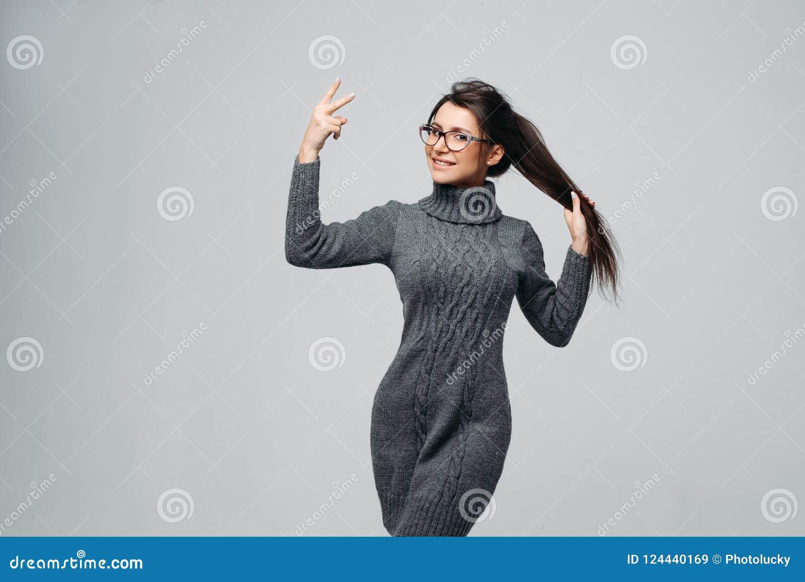 9b5b8cb3245 Stylish pretty girl posing at studio in fashionable dress. Isolated on gray  background
