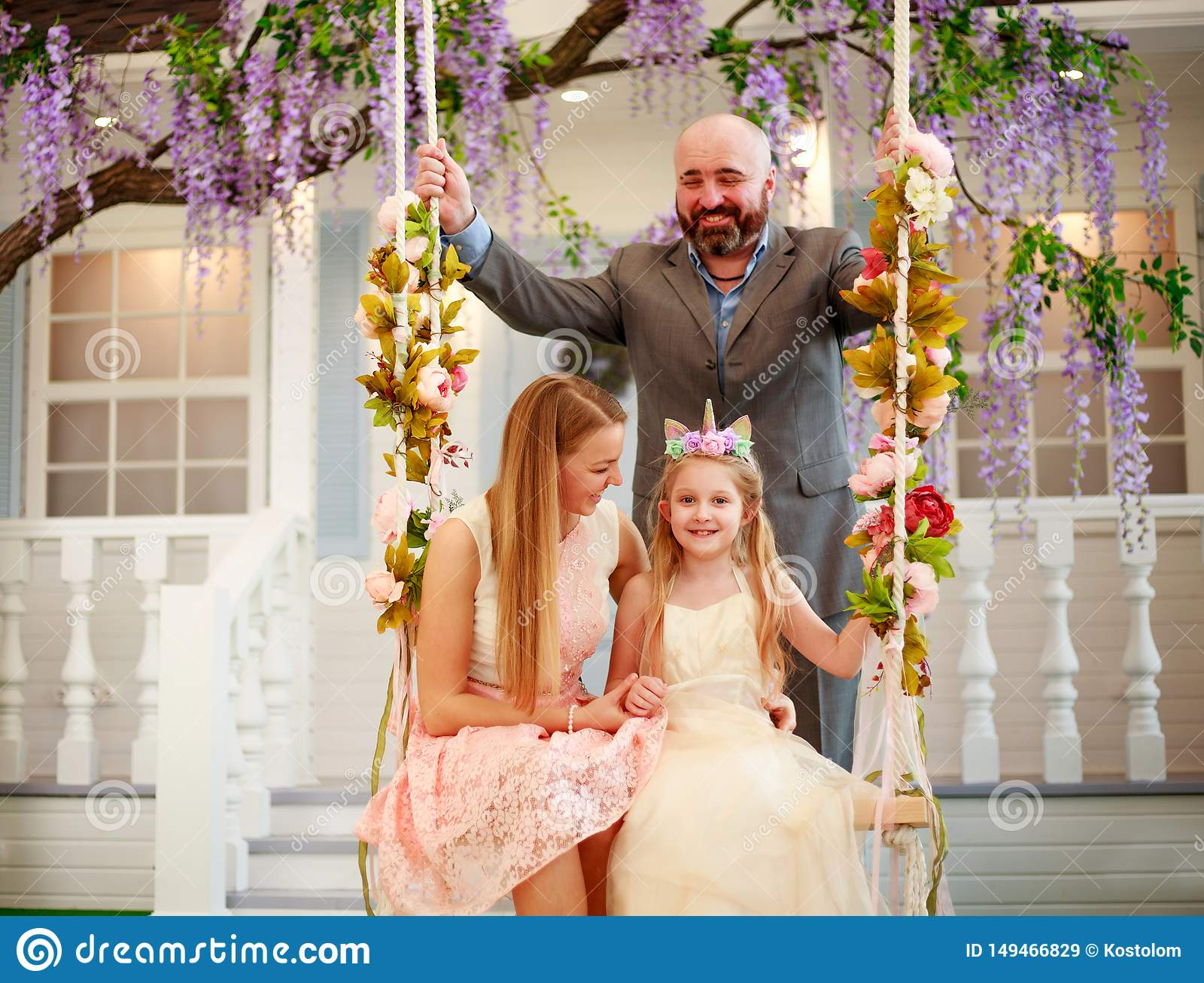Joyful family parents with daughter at home in blooming garden on swing