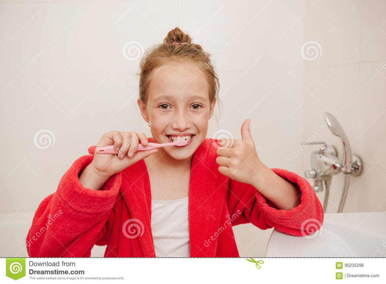 be0825eabe The girl in a dressing gown brushes teeth in a house bathroom. More similar  stock images