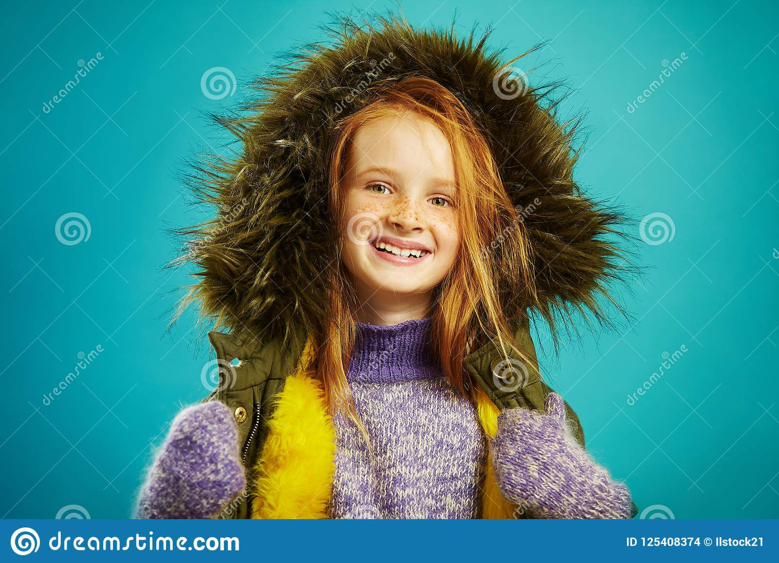 9cc8a2ef06972 Joyful girl of ten years in winter clothes over blue background. Red haired  child with beautiful freckles smiles, dressed in warm jacket, fur hood,  sweater, ...