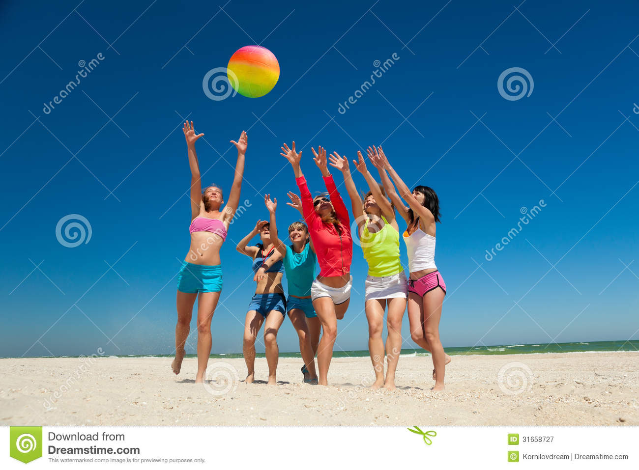 Group Of Young Joyful Girls Playing Volleyball Stock