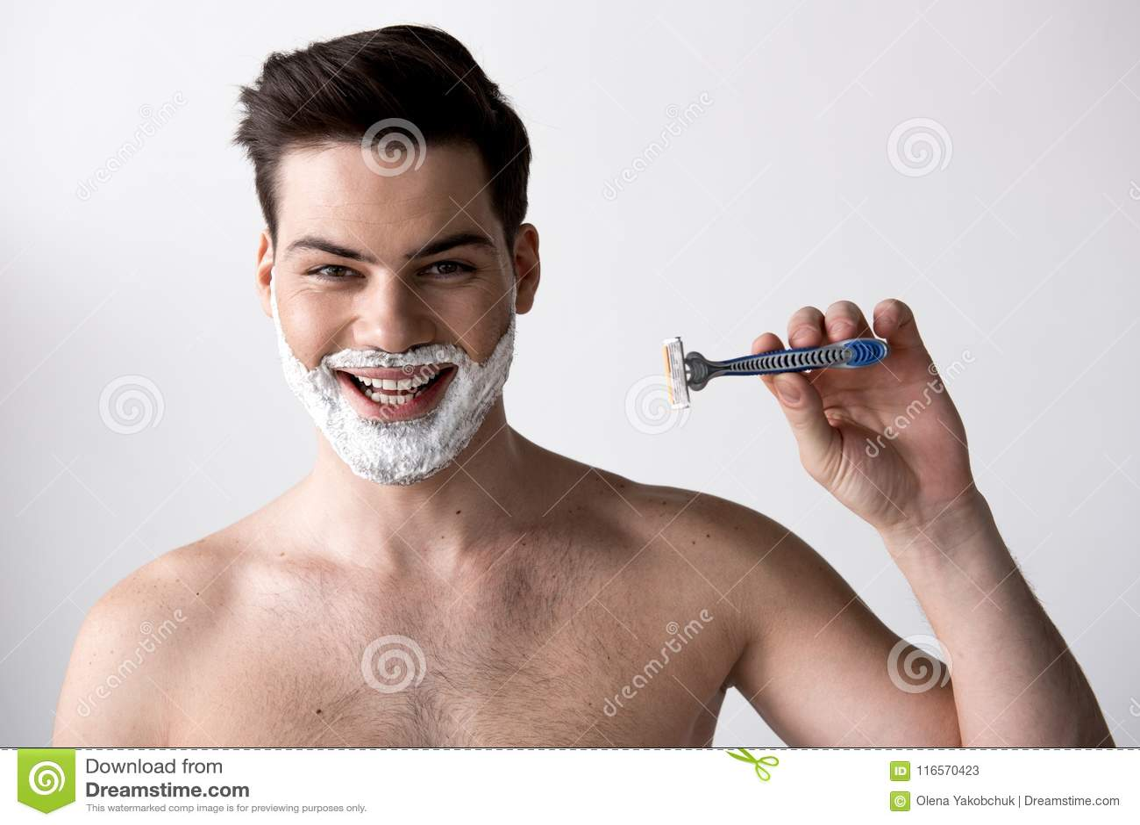 Joyful guy with shaving cream is expressing gladness