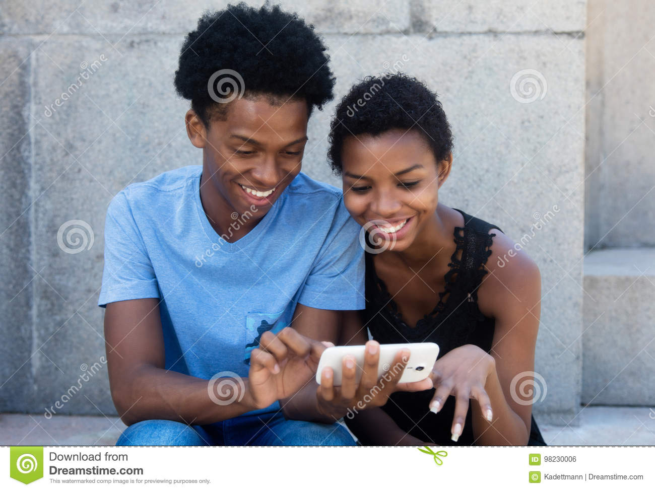 Joyful laughing african american couple looking at phone