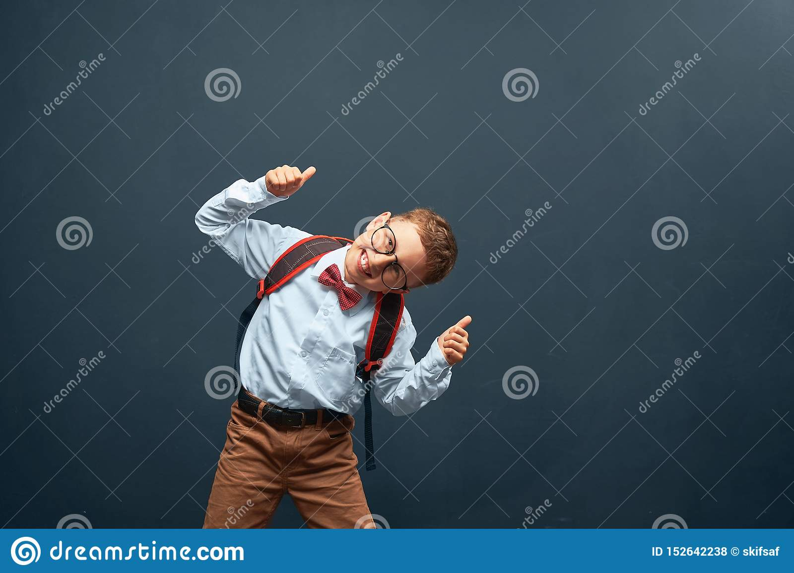 Joyful little boy, on a black background with a briefcase behind his shoulders shows a gesture of victory, joy of success. Happy