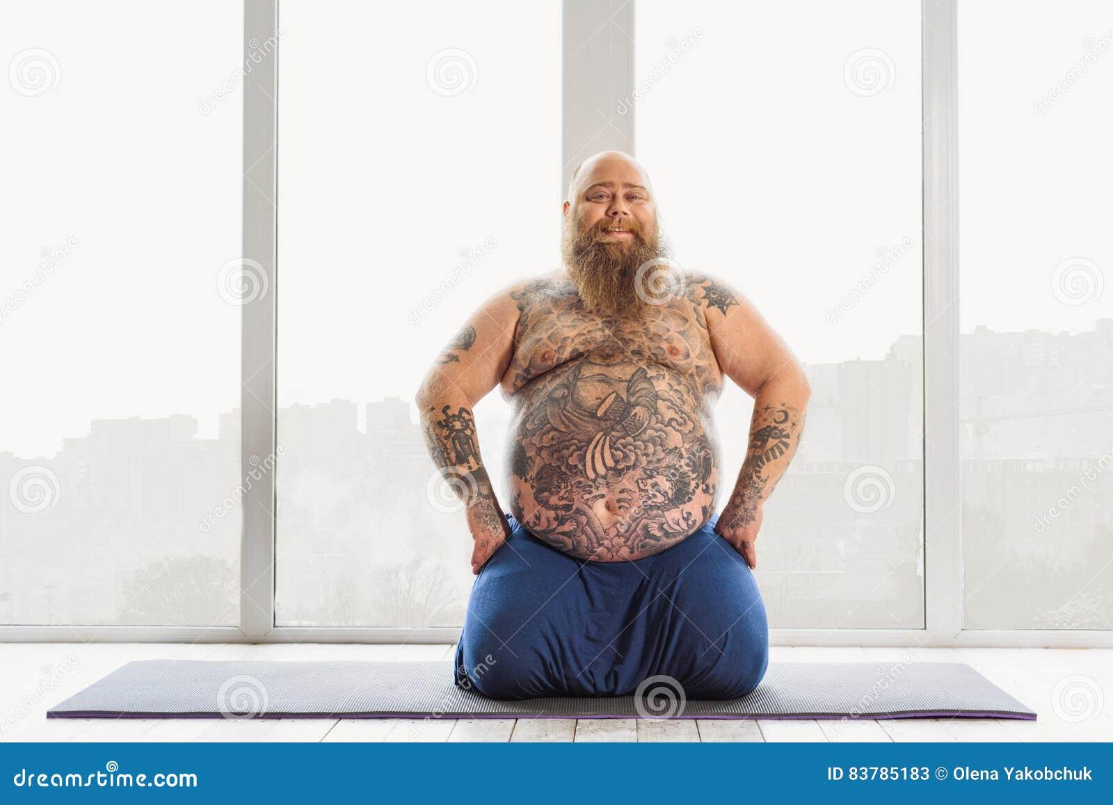 Joyful Mature Fat Man Doing Yoga At Home