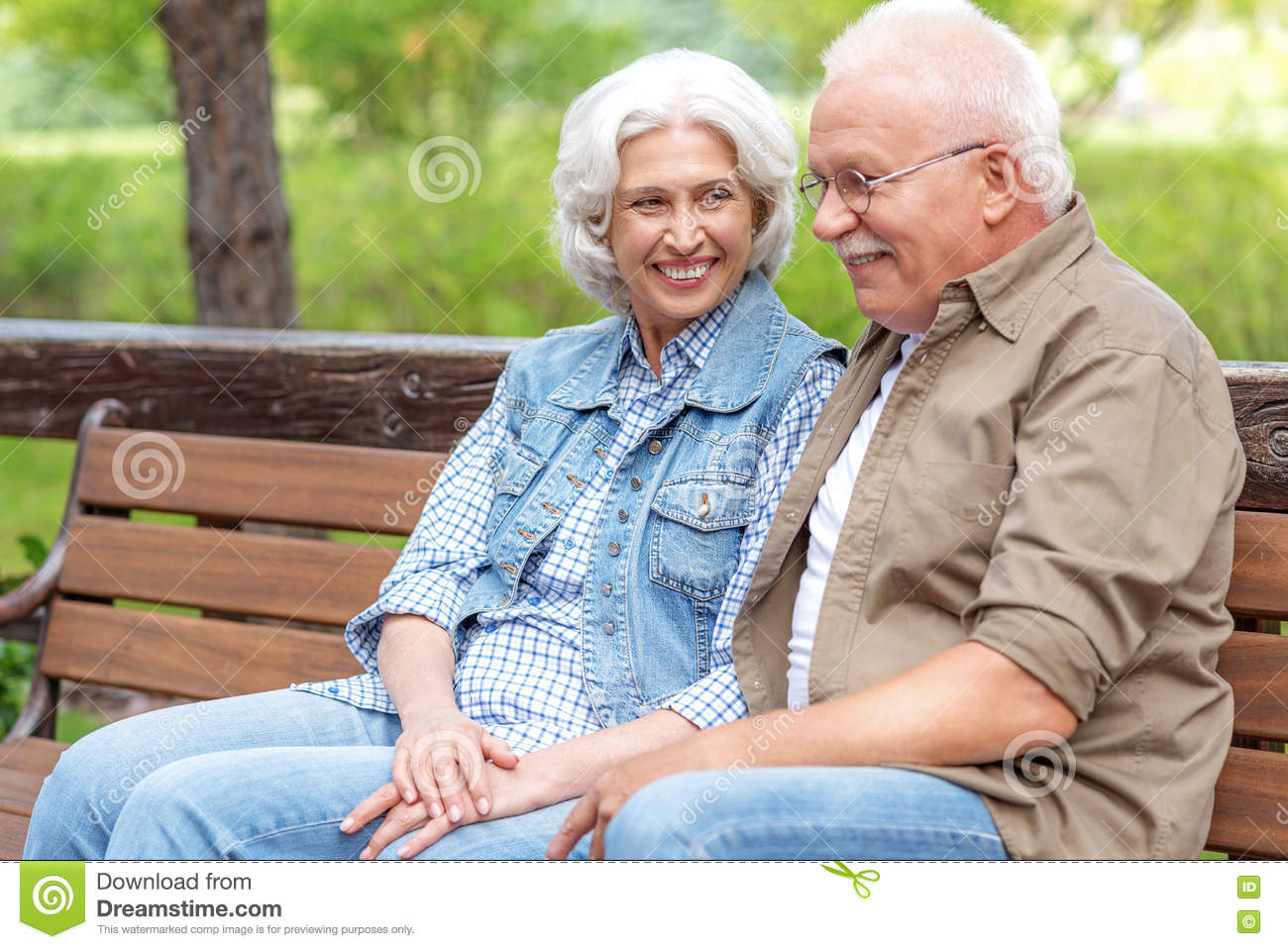 Happy old married couple is sitting on bench in park together. They are  holding hands and smiling