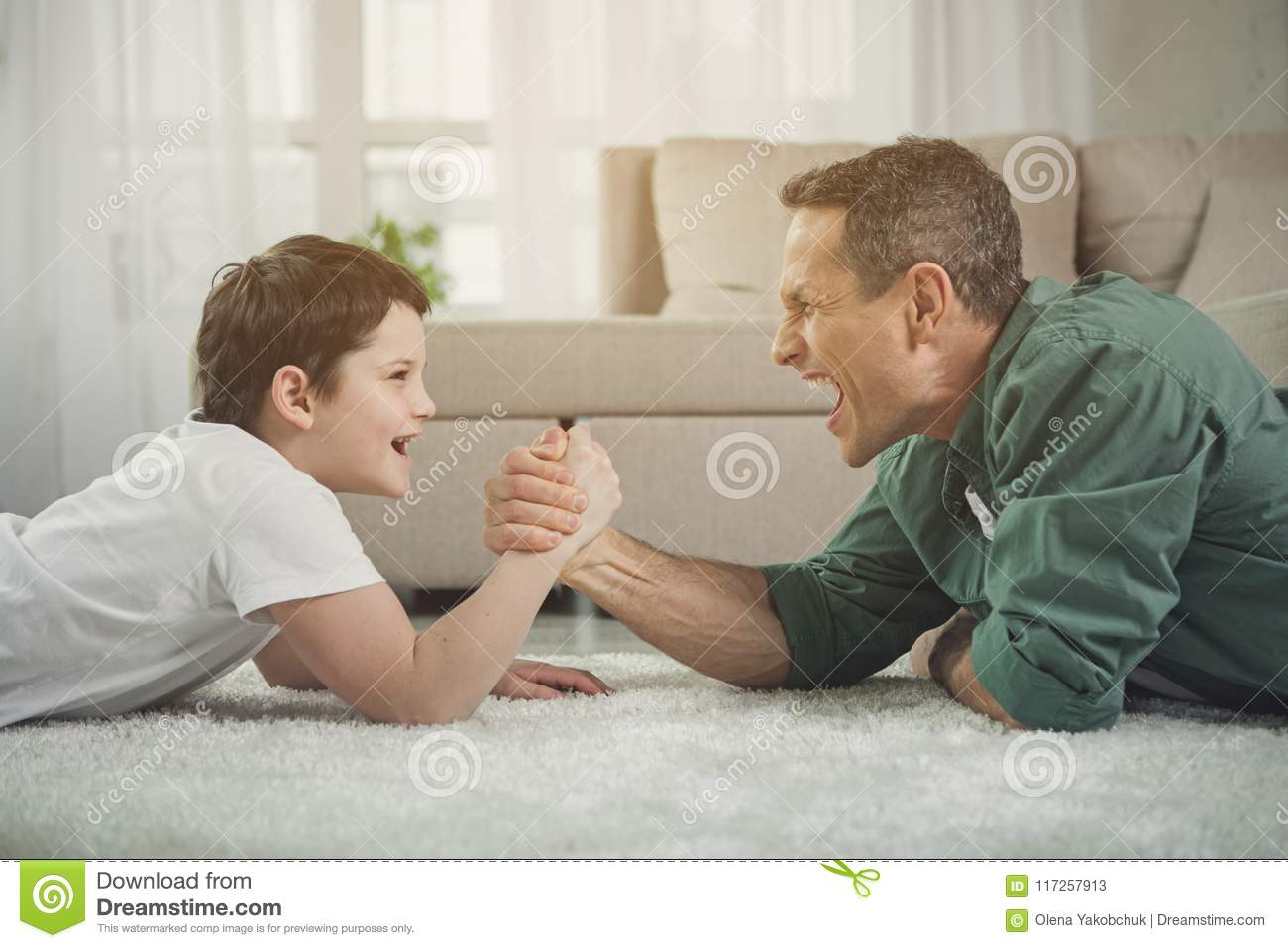 Cheerful father and son playing arm-wrestling at home