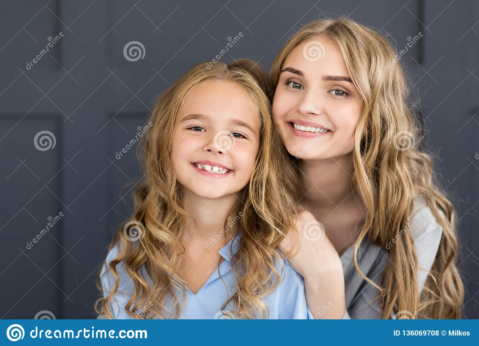 Joyful mother and daughter smiling at camera