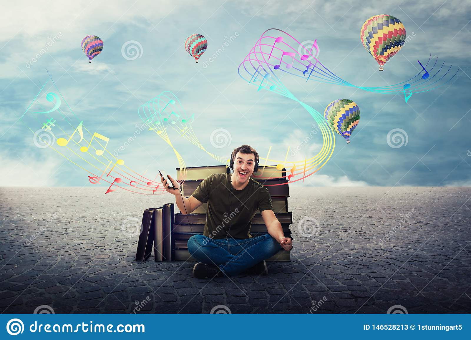 Joyful student guy seated relaxed on the floor listening to a song on headphones