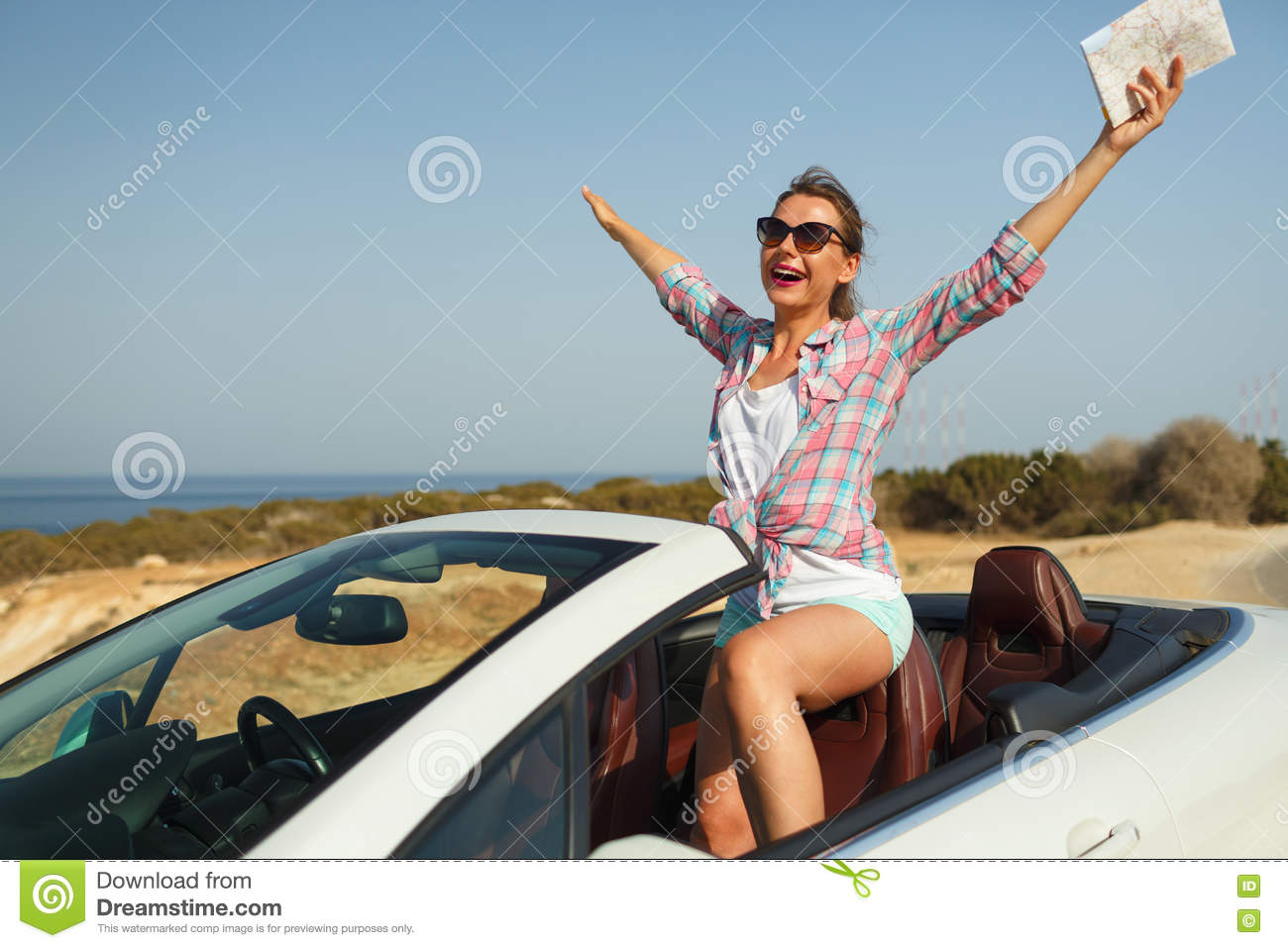 Joyful woman with a map in her hand traveling on a cabriolet