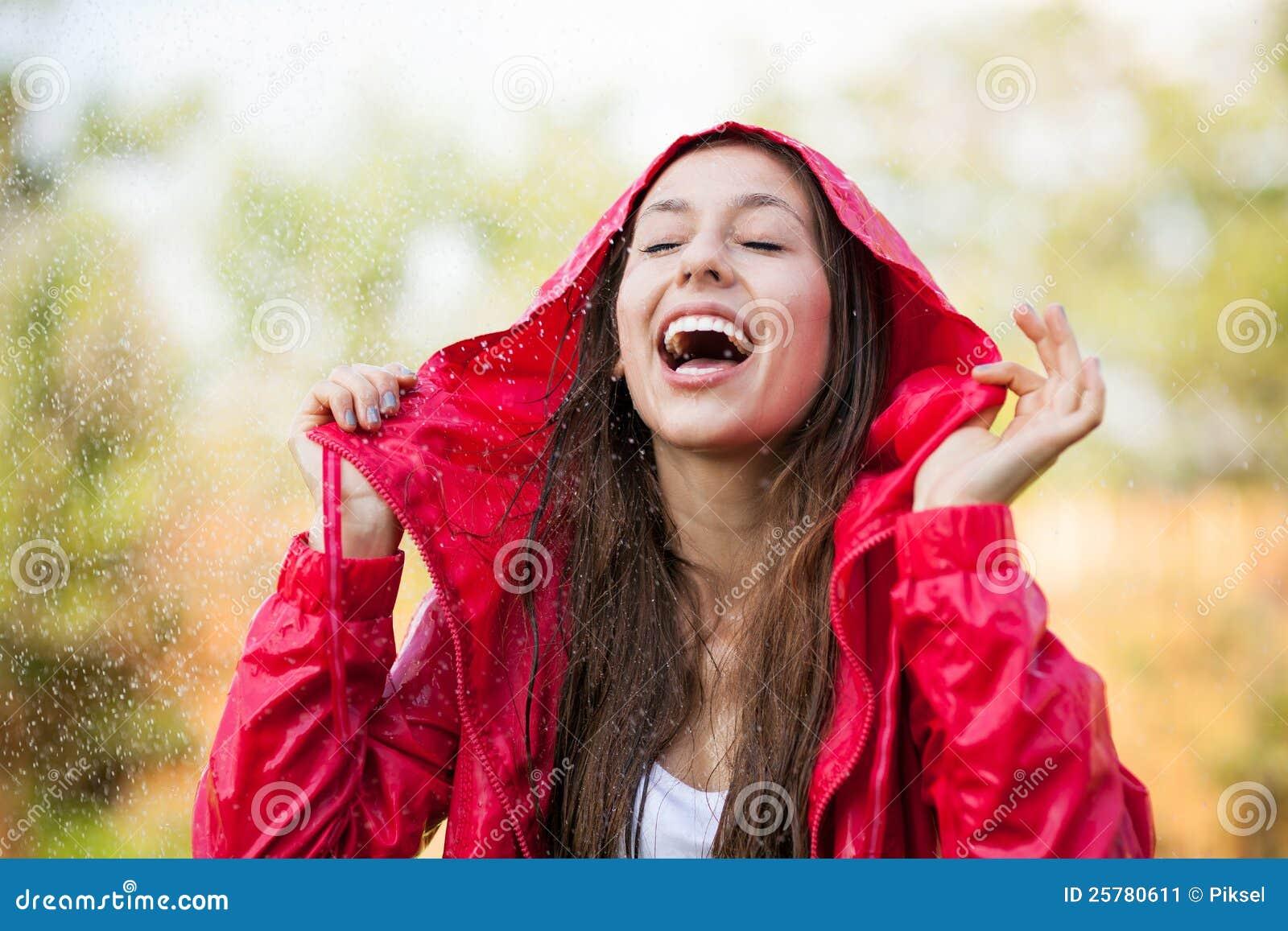 Joyful woman playing in rain