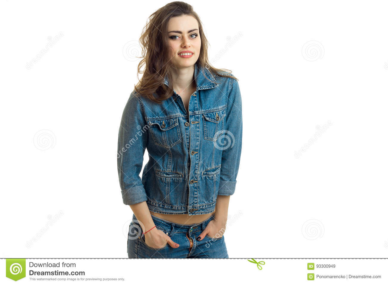 Joyful young girl stands in jeans jacket is smiling looks straight and keeps hands in his pockets