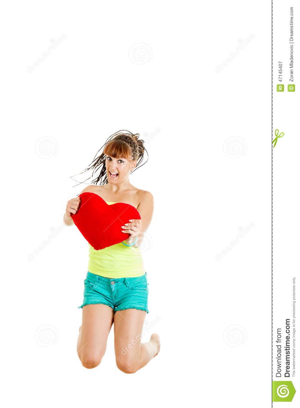 Joyful young woman with big heart jumping of surprise