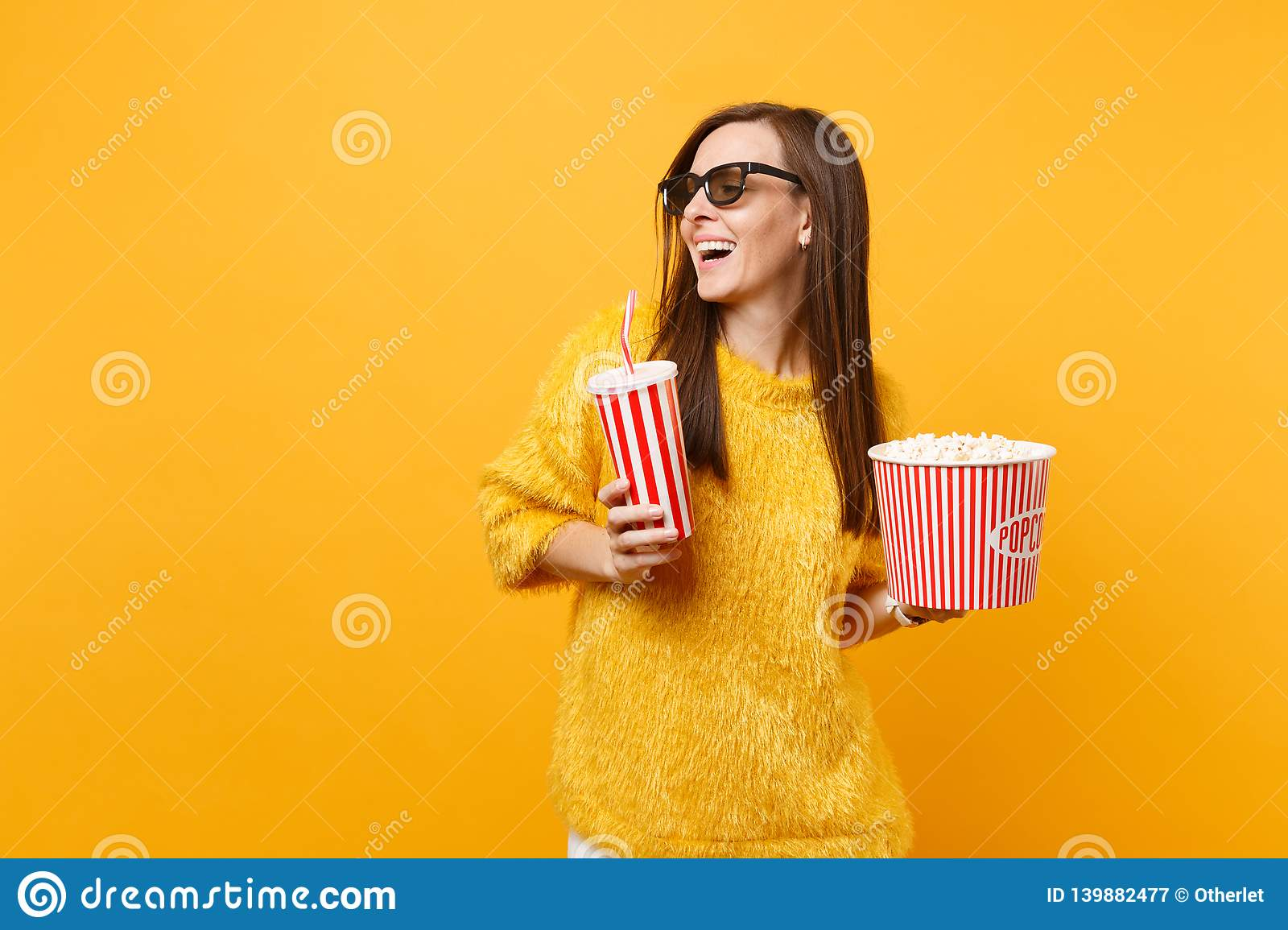 Joyful young woman in 3d imax glasses looking aside watching movie film hold bucket of popcorn, plastic cup of cola or
