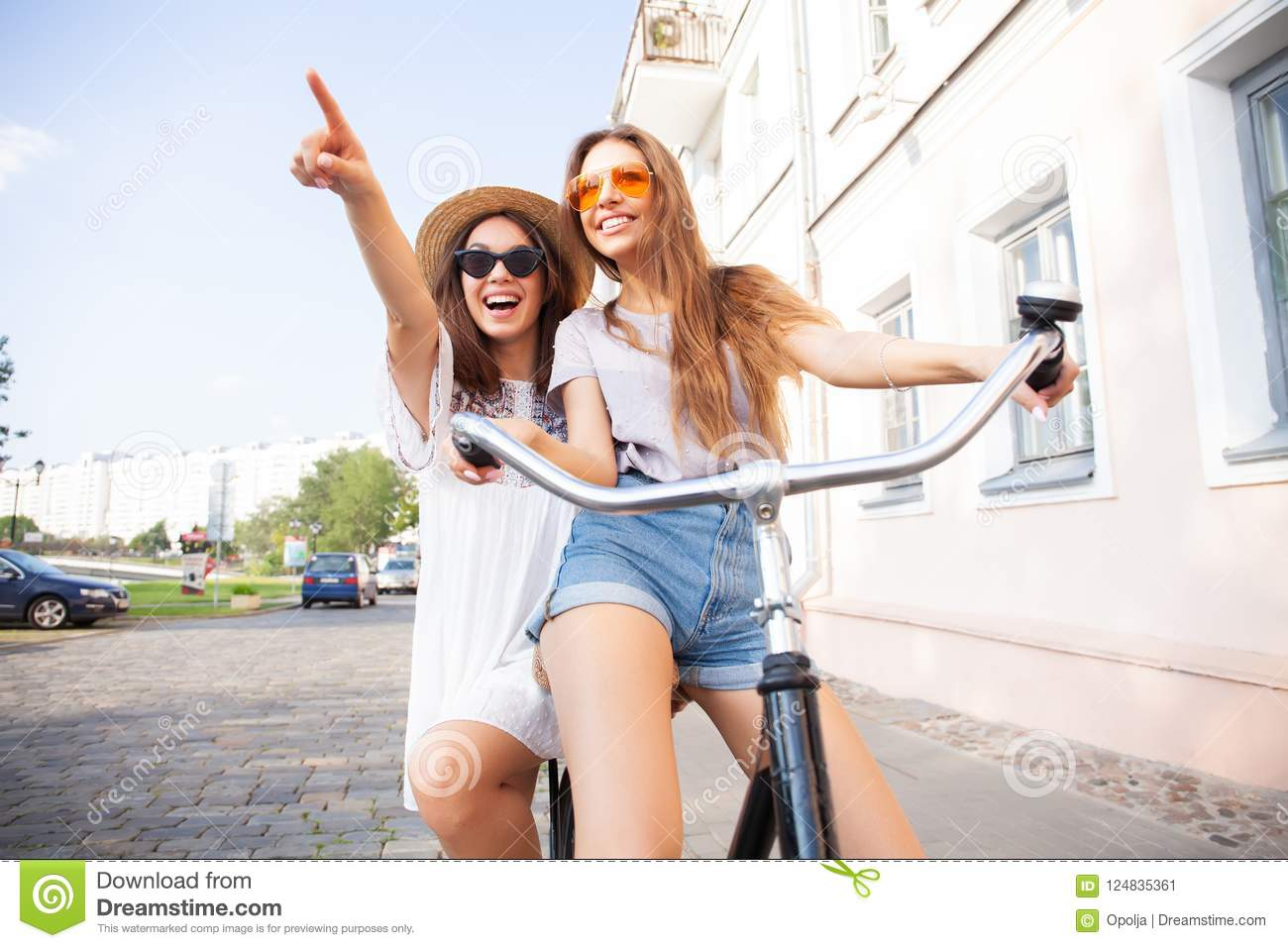 Joyful young women riding a bicycle together. Best friends having fun on a bike at the river promenade in the cit.