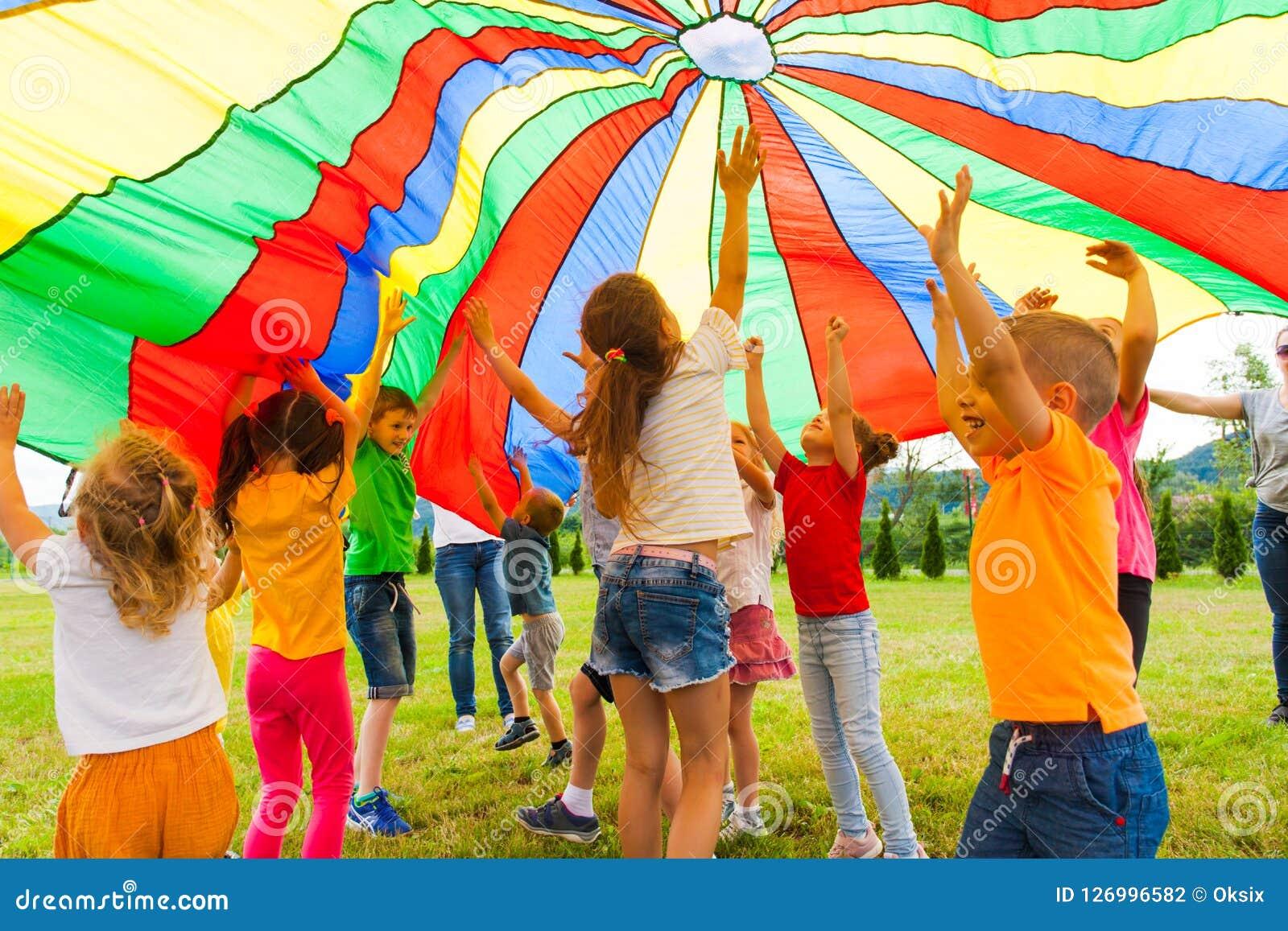 Joyous klasgenoten die onder kleurrijk valscherm in de zomer in openlucht springen