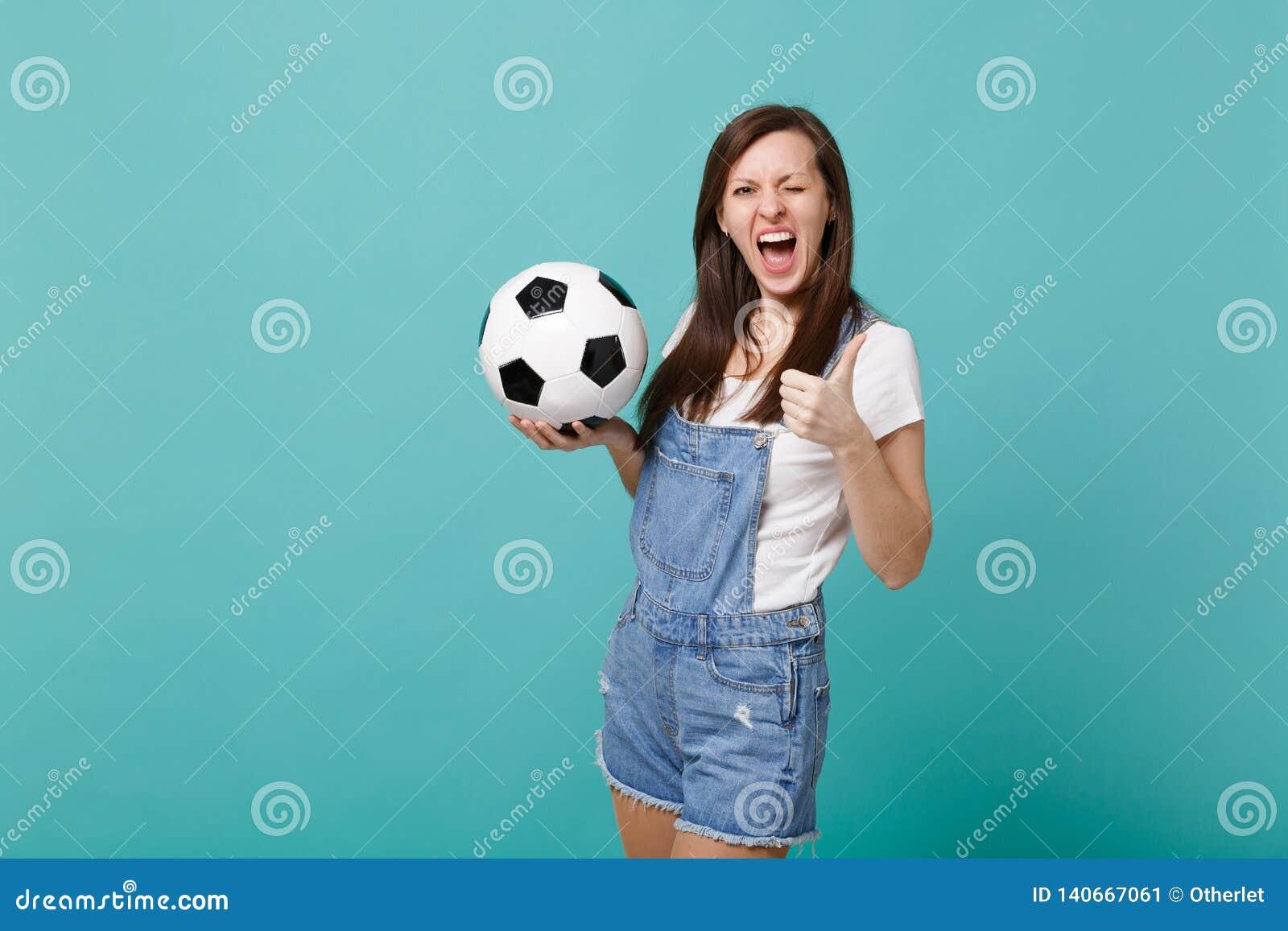 Jubel för blinkakvinnafotbollsfan upp det favorit- laget för service med tummen för visningen för fotbollbollen isolerade upp på