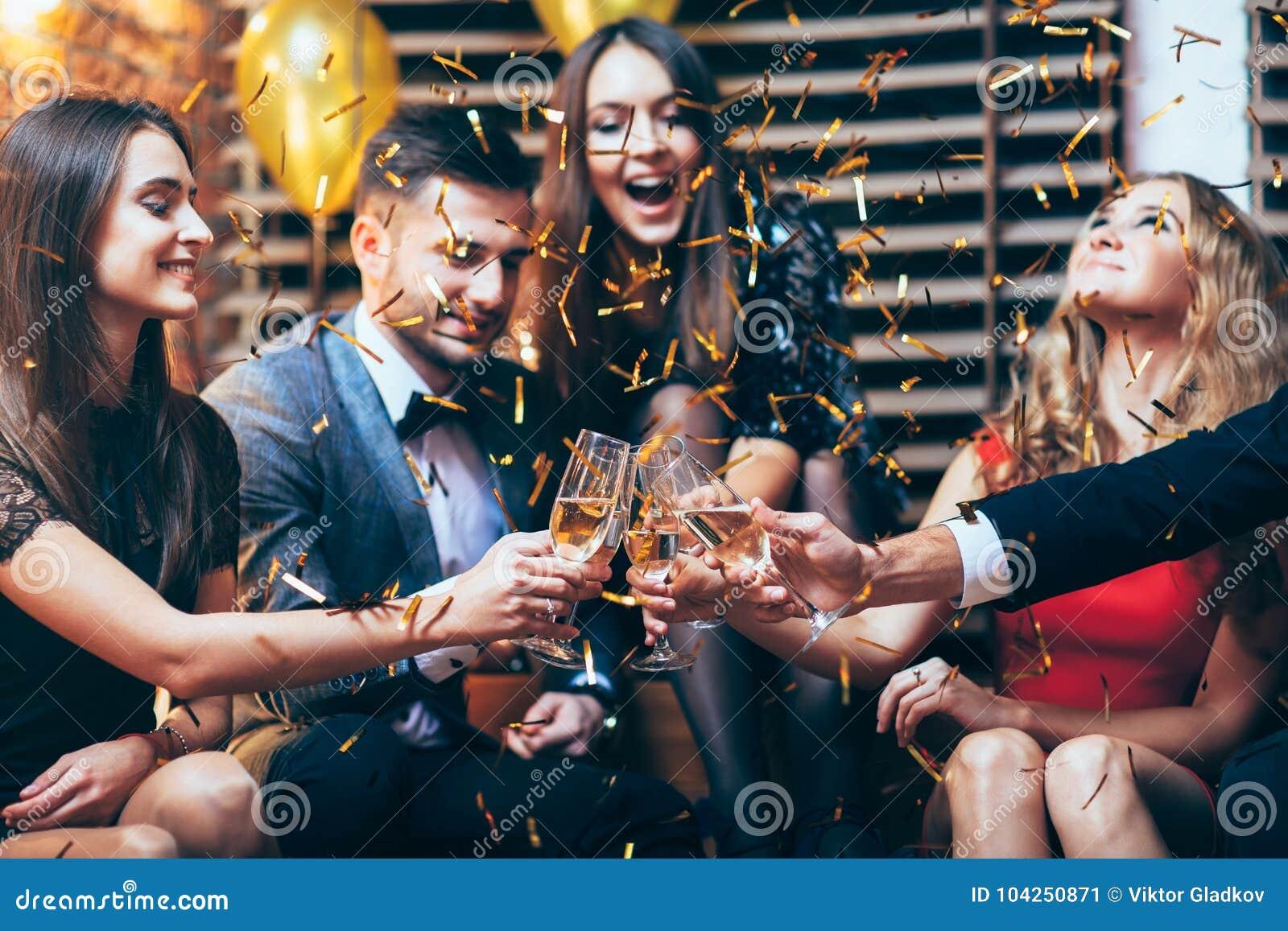 Jubel! Grupp av vänner som klirrar exponeringsglas av champagne under PA