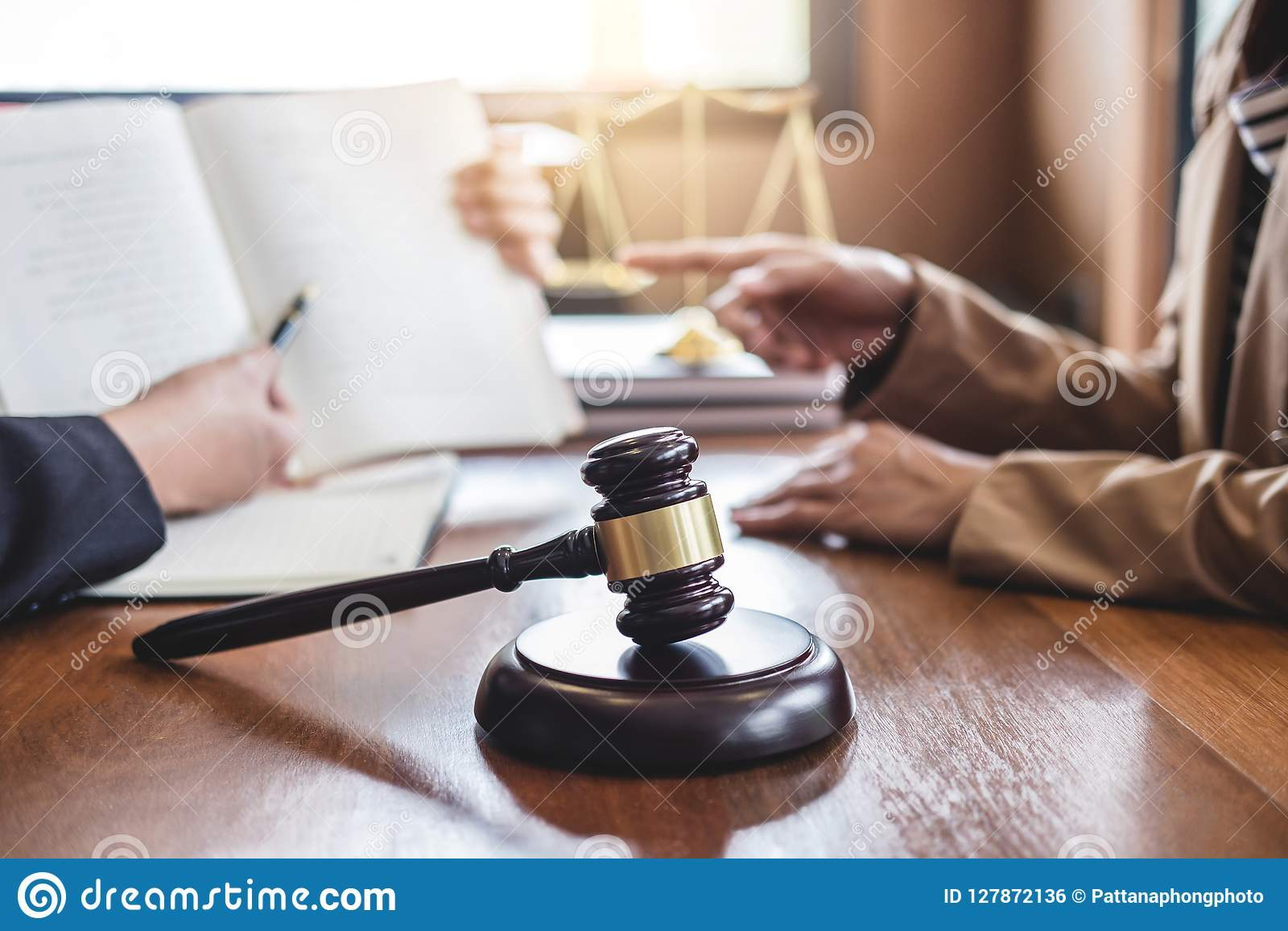 Judge gavel with scales of justice, Businesswoman and male lawyers or counselor discussing contract papers at law firm in office.