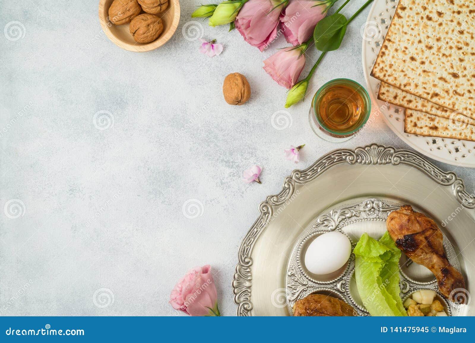 Judisk feriepåskhögtidbakgrund med matzoen, sederplattan och vårblommor