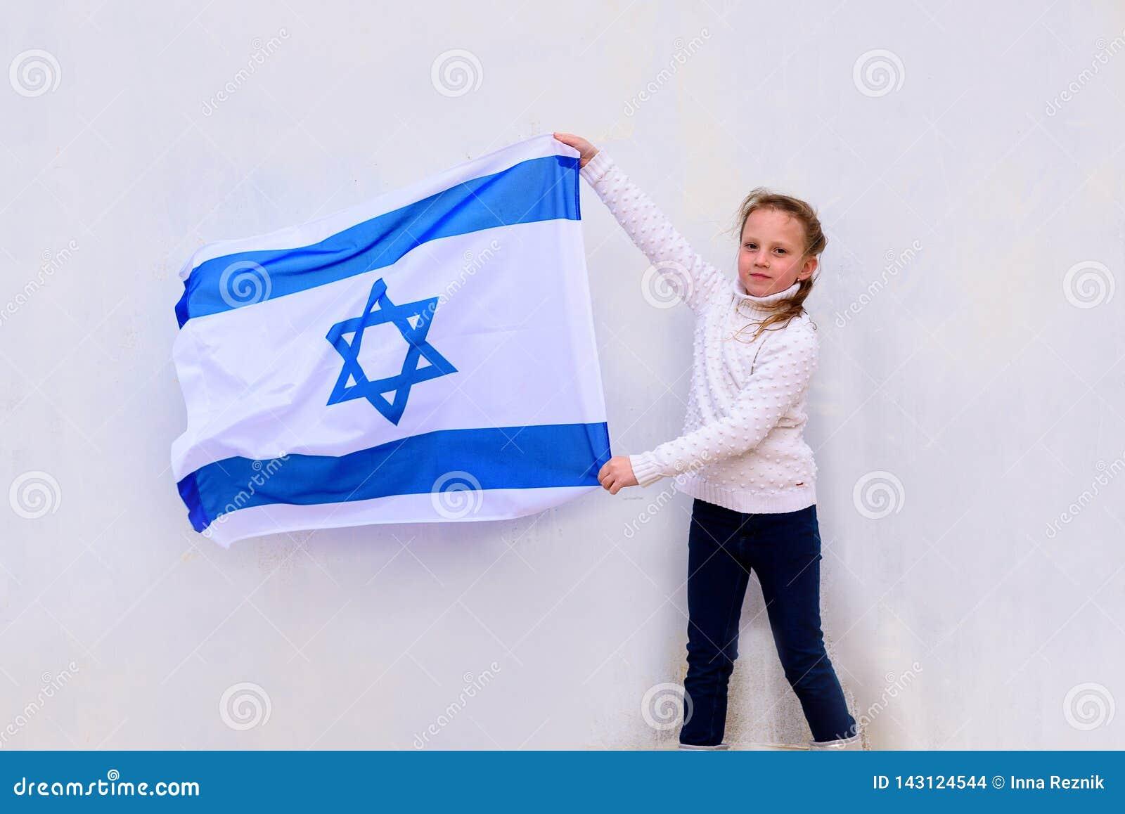 Judisk flicka för liten patriot med flaggan av Israel på vit bakgrund