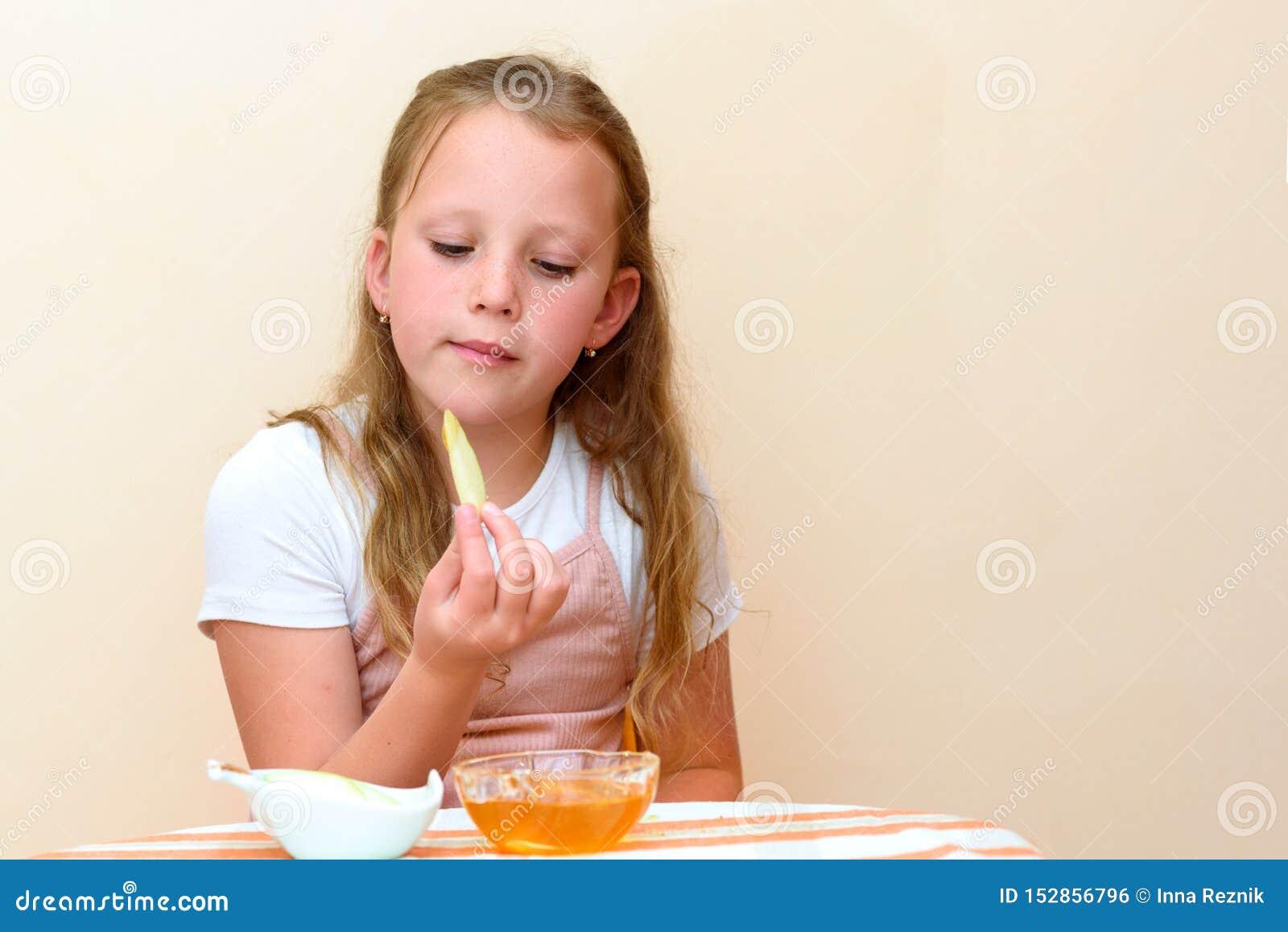 Judisk flicka som doppar äppleskivor in i honung på Rosh HaShanah
